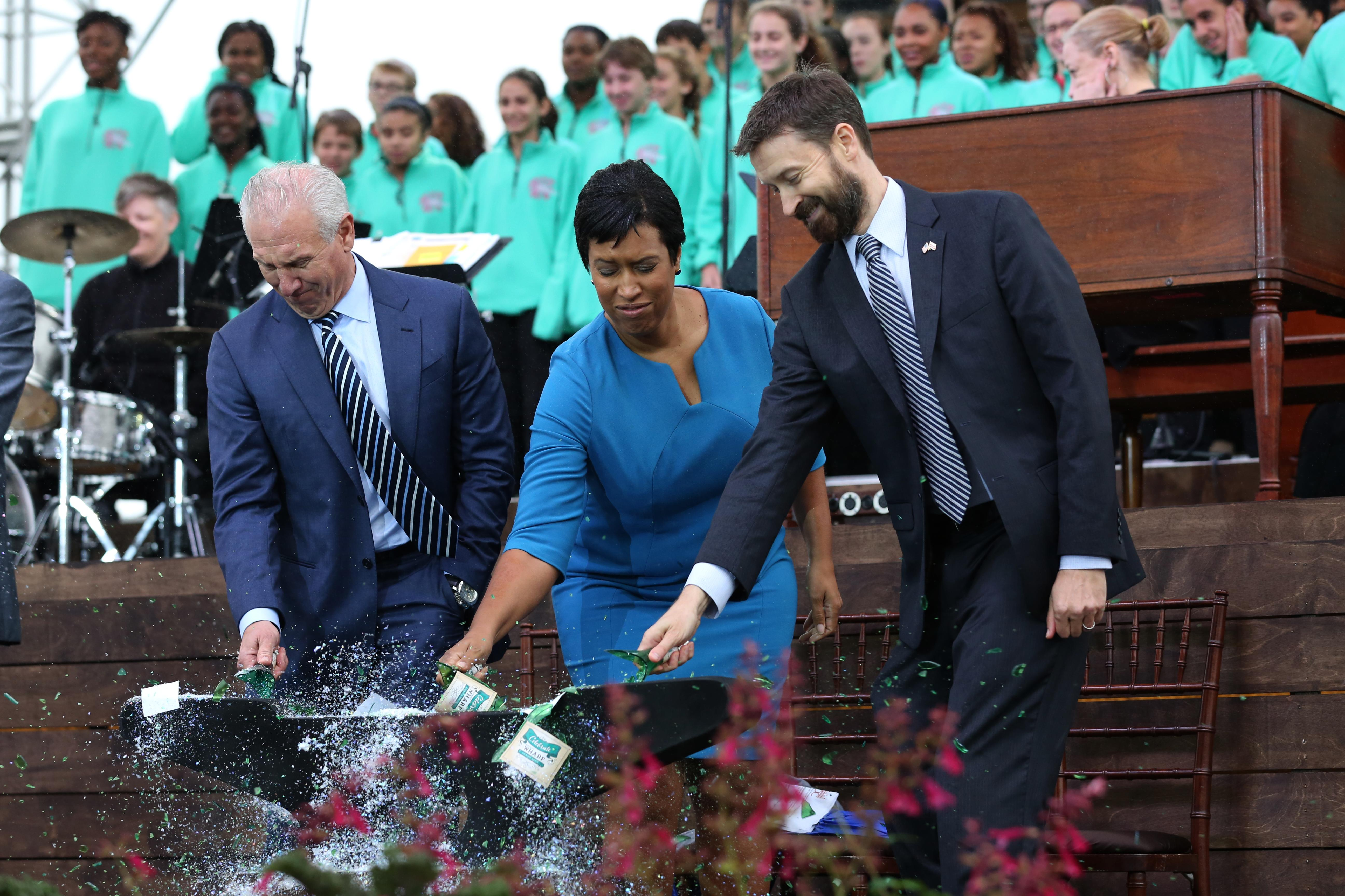 Developer Monty Hoffman, Mayor Muriel Bowser and Ward 6 council member Charles Allen christen The Wharf.{&amp;nbsp;} (Amanda Andrade-Rhoades/DC Refined)<p></p>