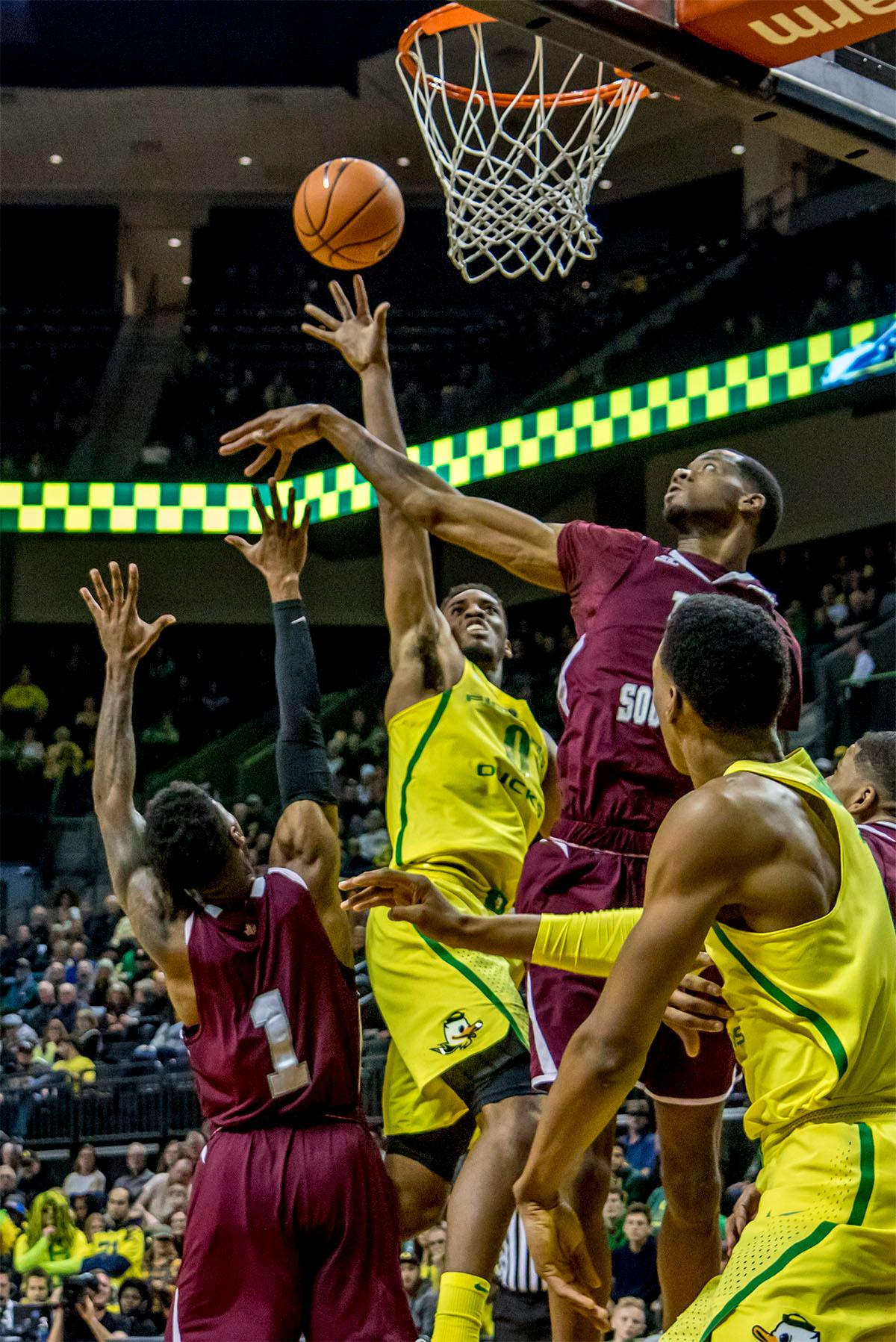 The Duck's Troy Brown (#0) makes a throw for the basket over the heads of several Tigers players. The Oregon Ducks defeated Texas Southern Tigers 74-68. The Ducks are now 7-3 overall in the Pac-12. Photo by August Frank. Oregon News Lab