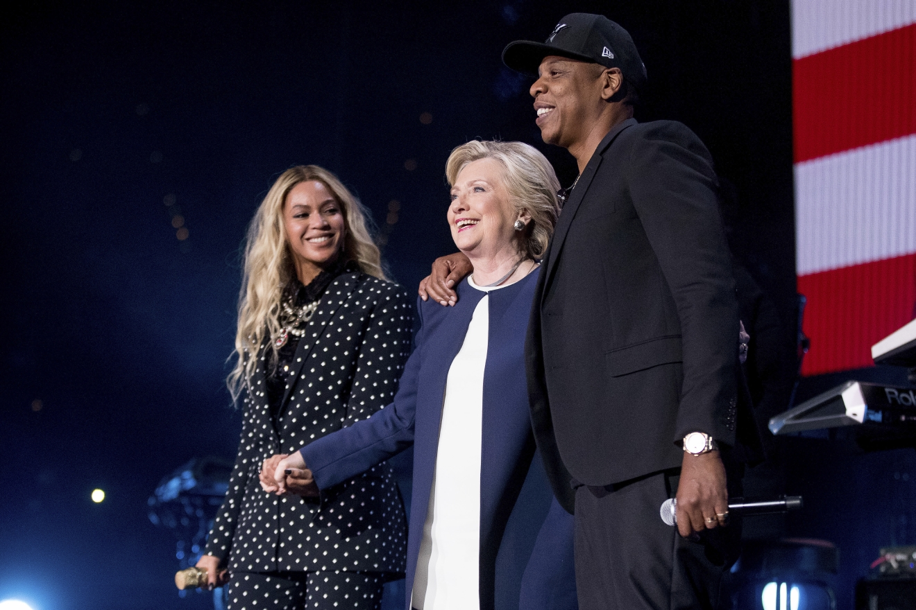 Democratic presidential candidate Hillary Clinton, center, appears on stage with artists Jay Z, right, and Beyonce, left, during a free concert at at the Wolstein Center in Cleveland, Friday, Nov. 4, 2016. (AP Photo/Andrew Harnik)