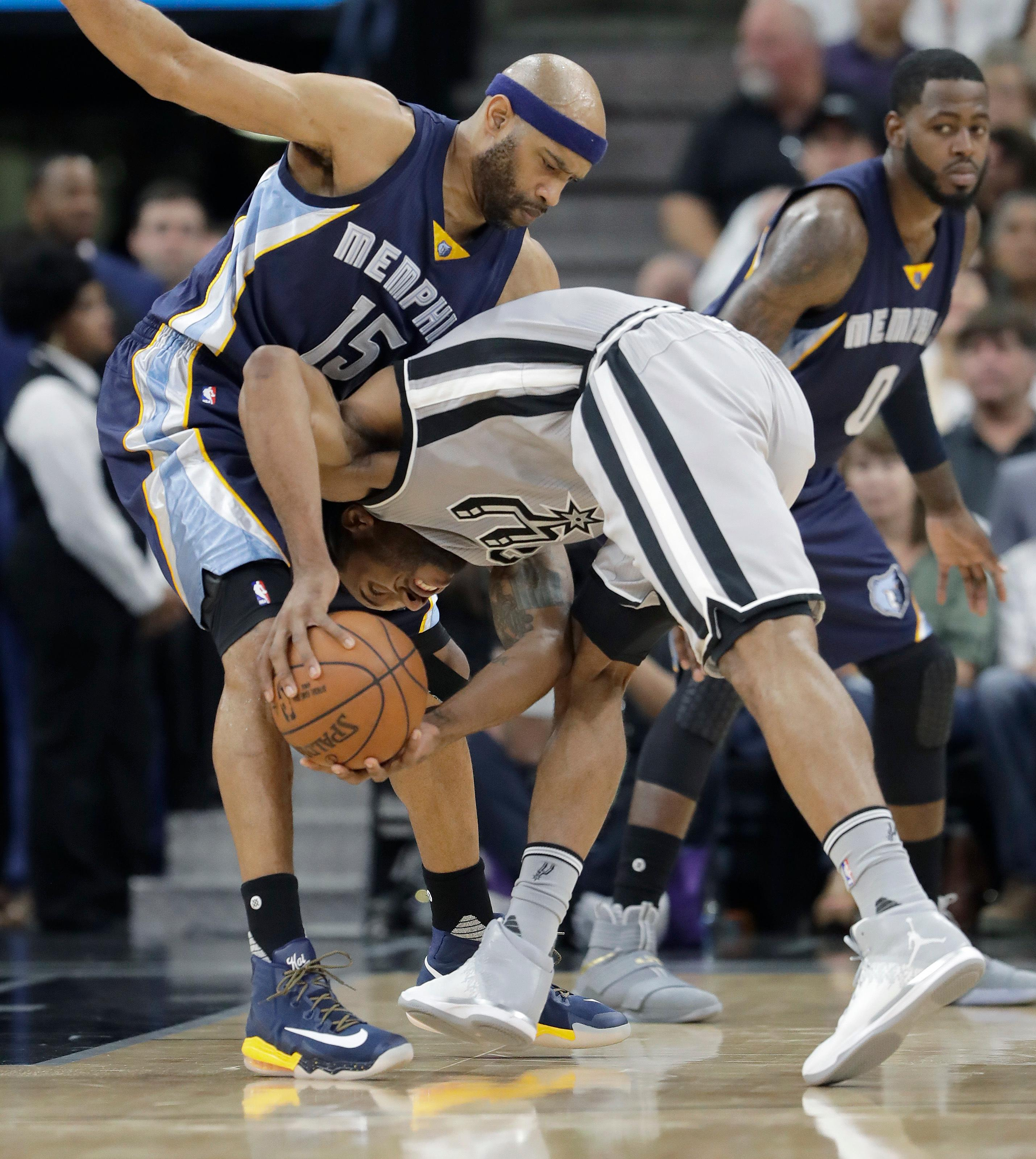 San Antonio Spurs forward Kawhi Leonard (2) crashed into Memphis Grizzlies guard Vince Carter (15) as he tries to drives to the basket during the first half of Game 1 of a first-round NBA basketball playoff series, Saturday, April 15, 2017, in San Antonio. (AP Photo/Eric Gay)