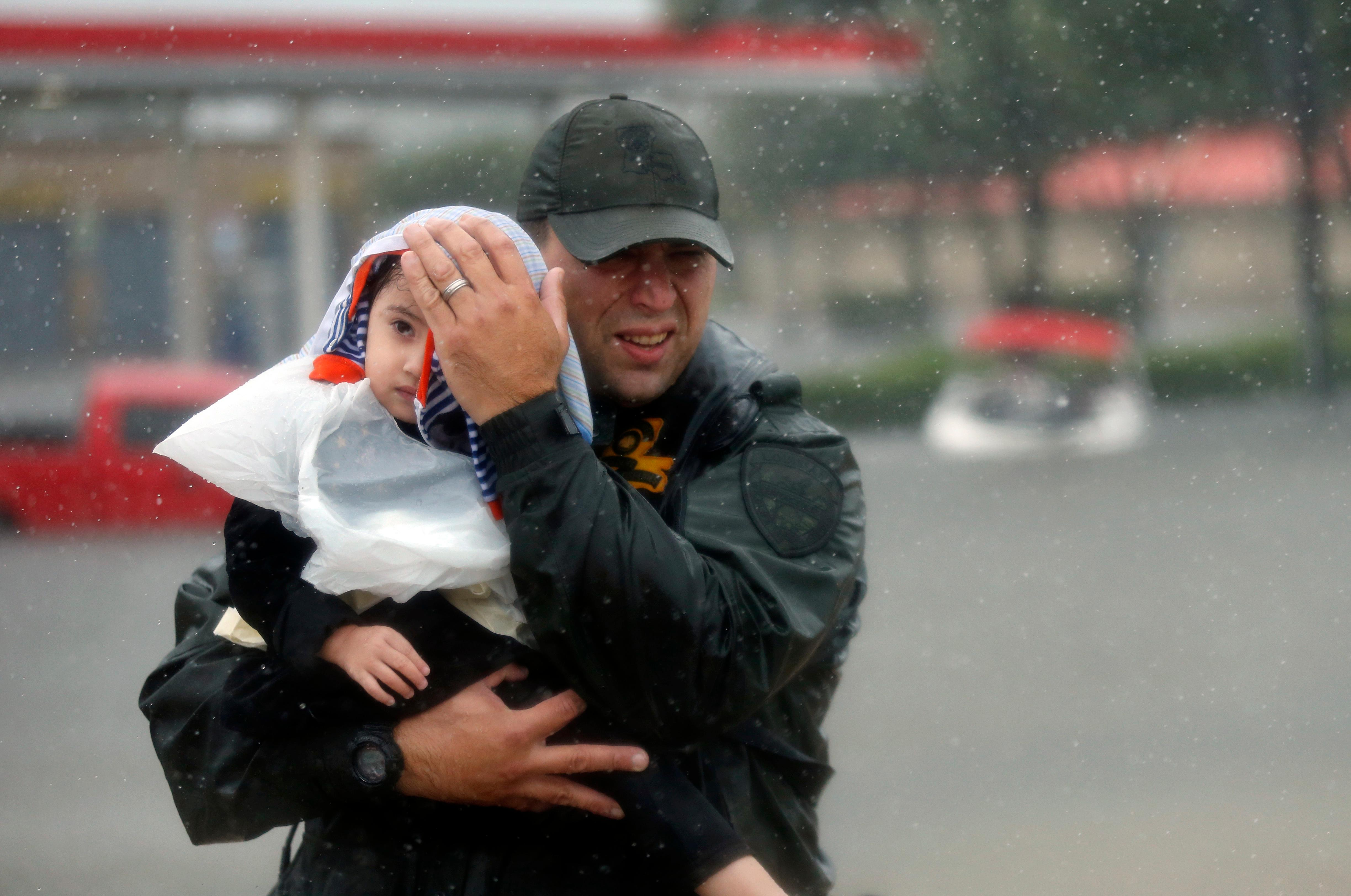 Sgt. Chad Watts, of the Louisiana Department of Wildlife and Fisheries, holds Madelyn Nguyen, 2, after he rescued her and her family by boat from floodwaters of Tropical Storm Harvey, which hit Texas last week as a Category 4 hurricane, in Houston, Monday, Aug. 28, 2017. (AP Photo/Gerald Herbert)