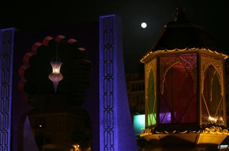 A perigee moon, also known as a supermoon, centre, appears between traditional Ramadan lanterns that decorate a building in Beirut, Lebanon, Saturday, July 12, 2014.