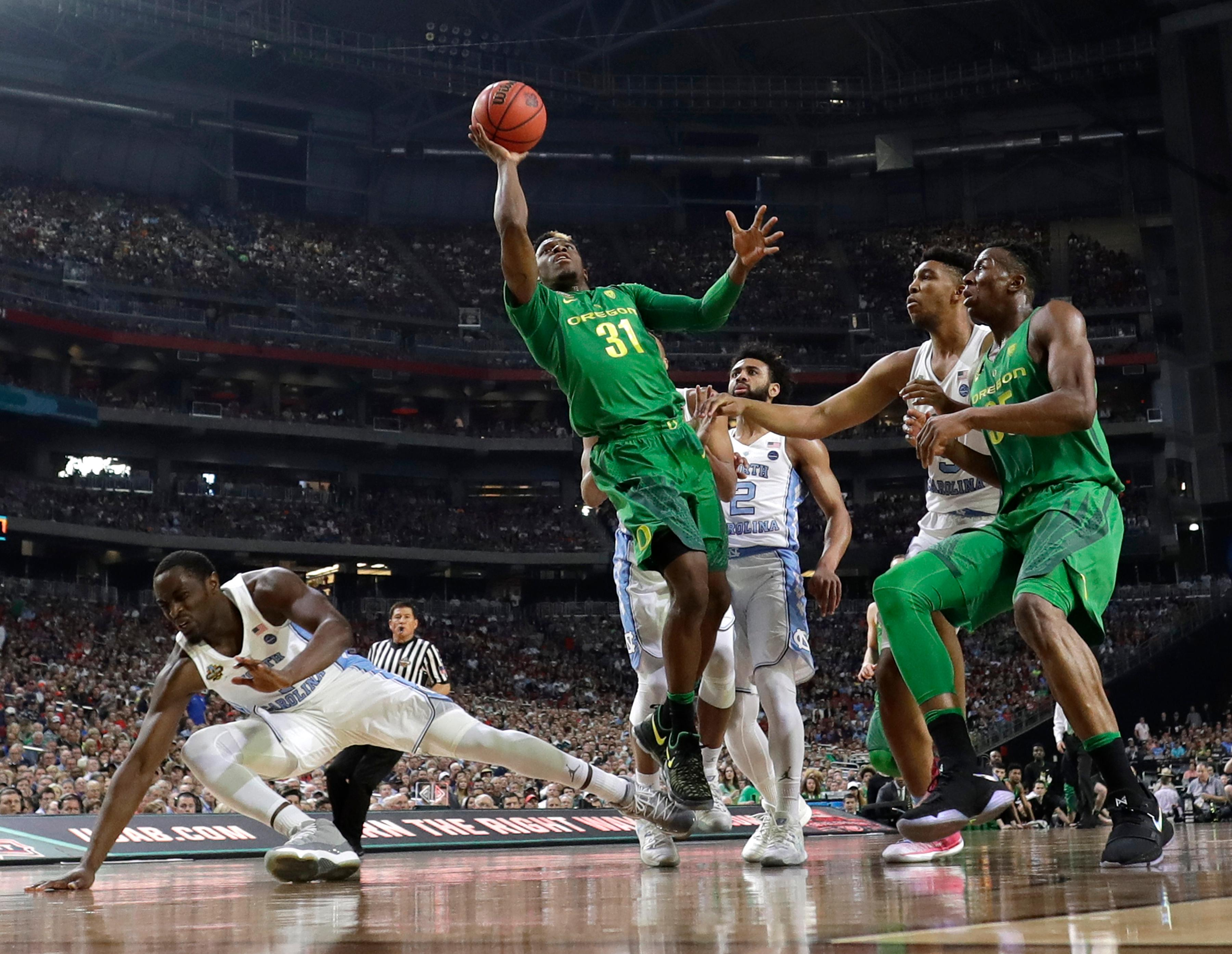 Oregon guard Dylan Ennis (31) drives to the basket over North Carolina forward Theo Pinson, left, during the first half in the semifinals of the Final Four NCAA college basketball tournament, Saturday, April 1, 2017, in Glendale, Ariz. (AP Photo/David J. Phillip)