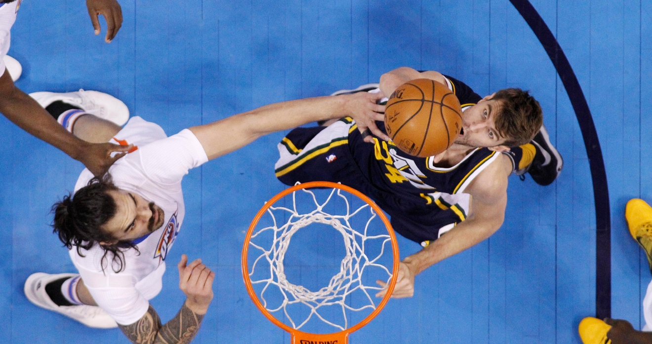 Utah Jazz center Jeff Withey, right, shoots as Oklahoma City Thunder center Steven Adams, left, defends during the second quarter of an NBA basketball game in Oklahoma City, Thursday, March 24, 2016. (AP Photo/Sue Ogrocki)