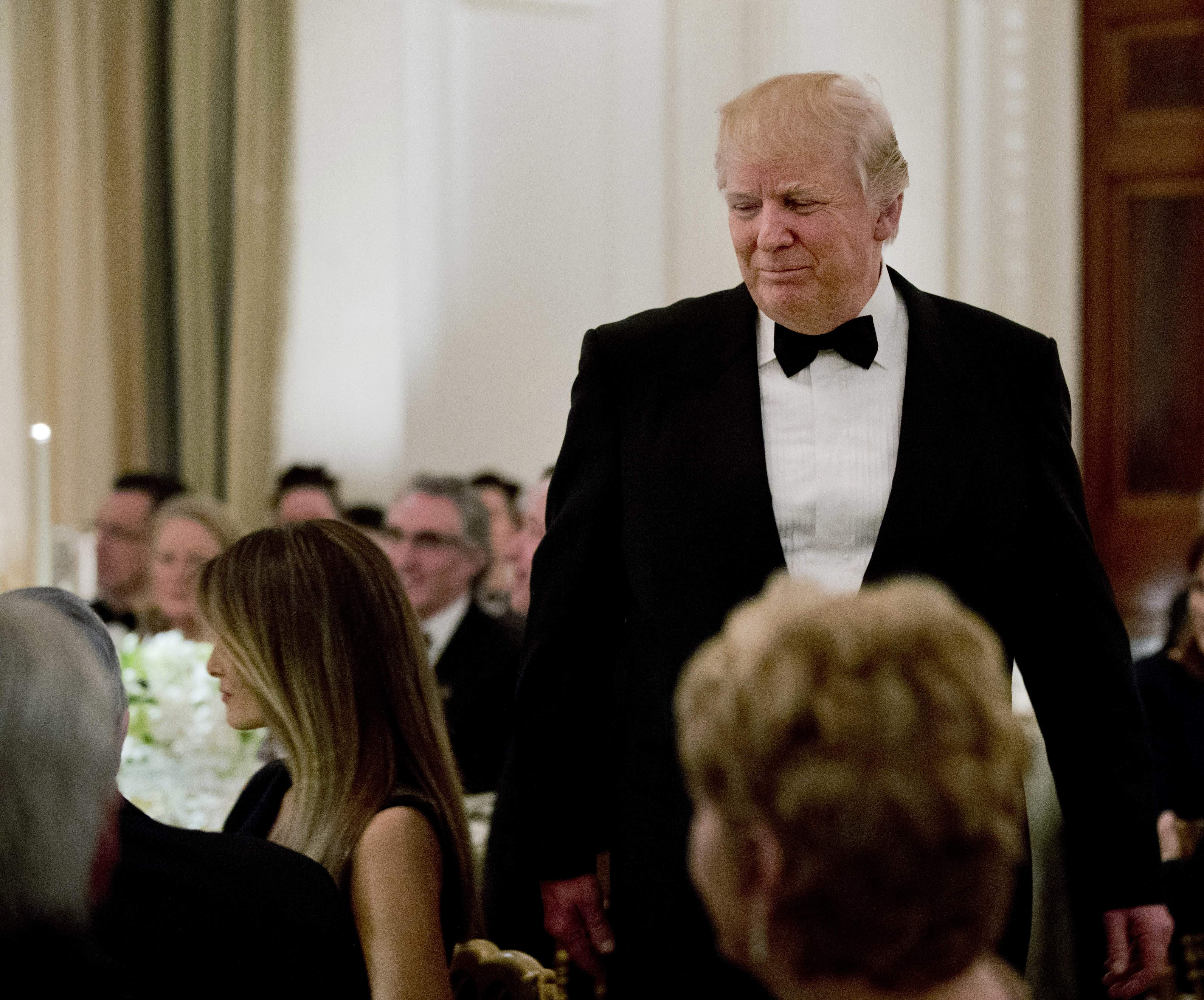 DAY 38 - In this Feb. 26, 2017, file photo, President Donald Trump walks towards first lady Melania Trump, left, after speaking at a dinner reception for the governors during the annual National Governors Association winter meeting at the State Dining Room of the White House in Washington. (AP Photo/Manuel Balce Ceneta, File)