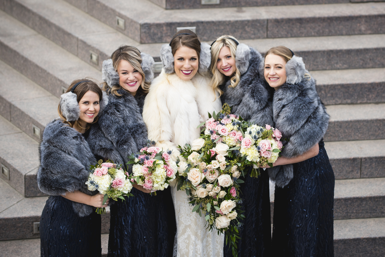 Michelle says the wedding will go down as one of the coldest she has ever photographed and she even had to bring hand warmers for portraits! Thank goodness Bonnie had gorgeous fur wraps and adorable earmuffs for her bridal party! (Image: Michelle Lindsay Photography)