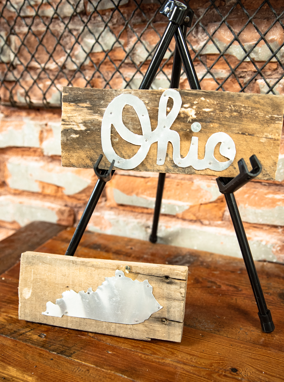 Sara Cole of Sara Cole Art Designs creates rustic wall hangings using reclaimed pallet and barn wood with detailed cut aluminum. Her work pays homage to the region and its charms, such as the Roebling bridge, Kentucky bourbon, and the great outdoors. / Image: Melissa Sliney // Published: 6.26.19