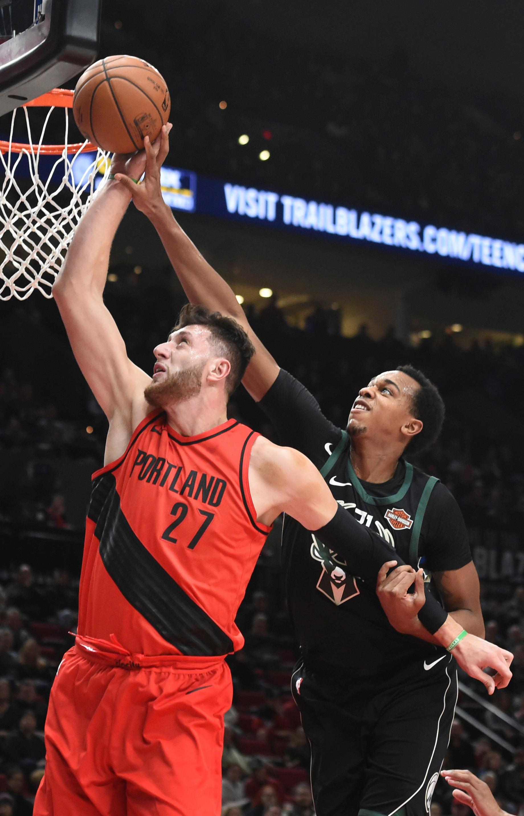 Portland Trail Blazers center Jusuf Nurkic grabs a rebound in front of Milwaukee Bucks forward John Henson during the first quarter of an NBA basketball game in Portland, Ore., Thursday, Nov. 30, 2017. (AP Photo/Steve Dykes)