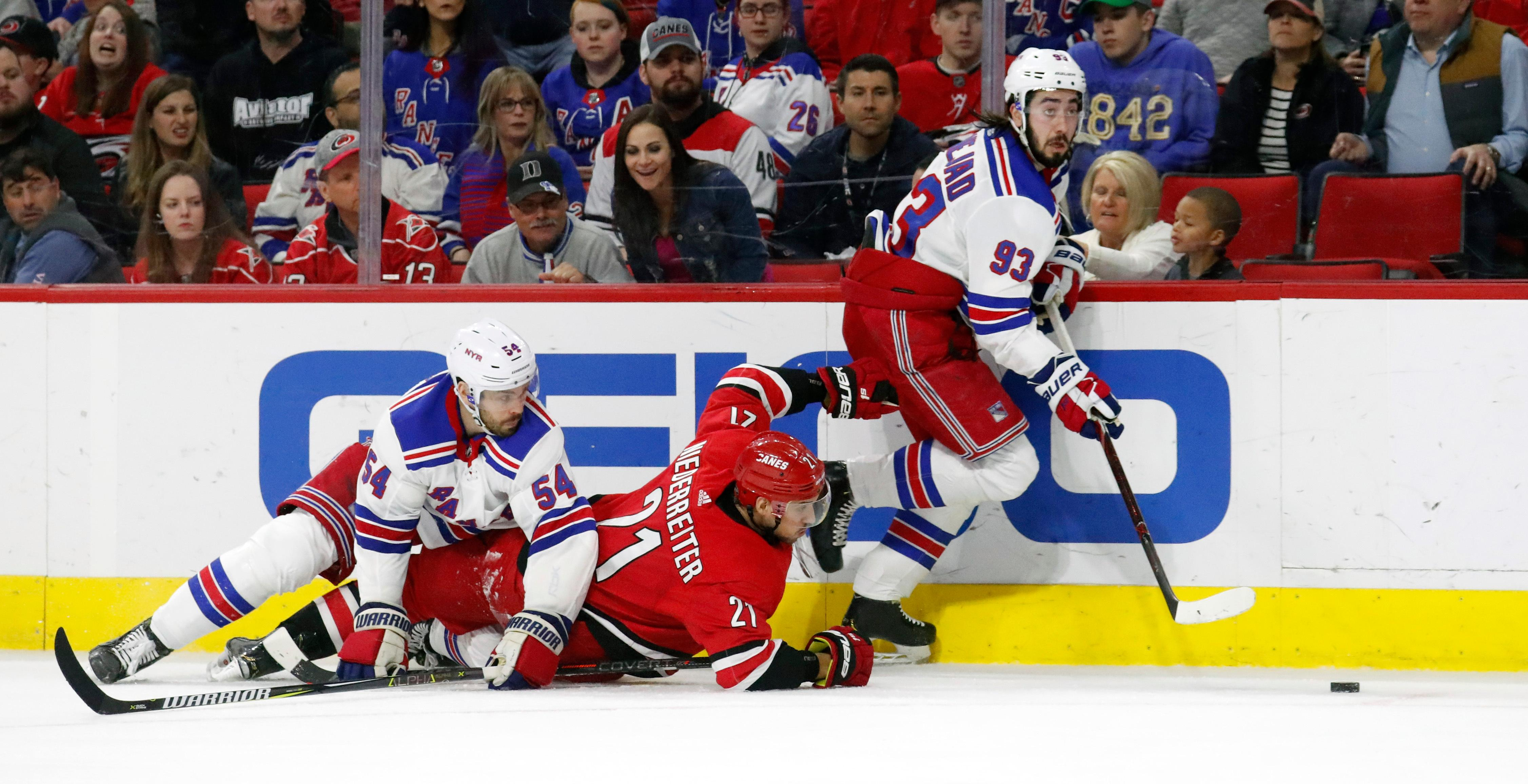 Carolina Hurricanes' Nino Niederreiter (21) of Switzerland battles the New York Rangers' Adam McQuaid (54) and Mika Zibanejad (93) of Sweden for the puck during the second period of an NHL hockey game in Raleigh, N.C., Tuesday, Feb. 19, 2019. (AP Photo/Chris Seward)