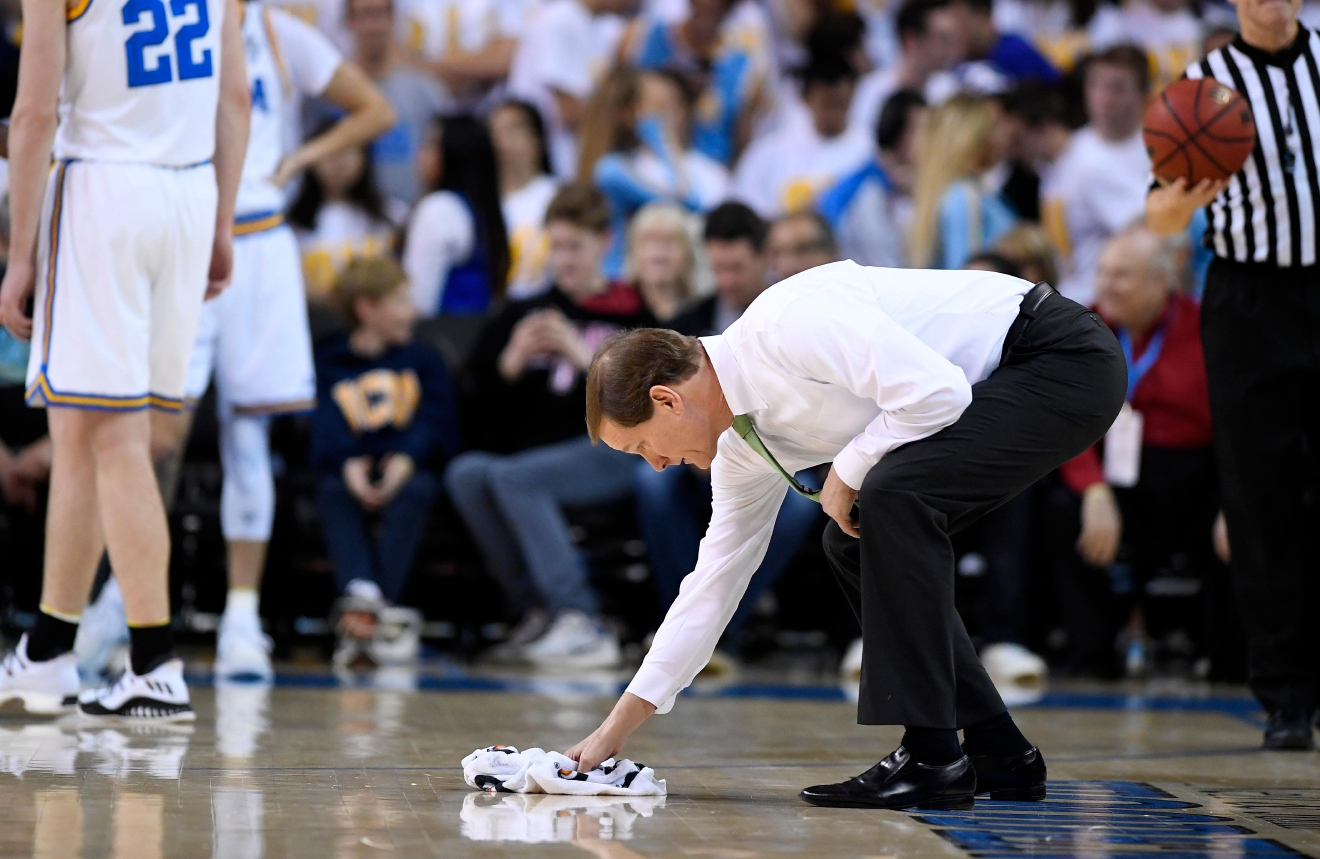Oregon head coach Dana Altman wipes the floor during the first half of an NCAA college basketball game against UCLA, Thursday, Feb. 9, 2017, in Los Angeles. (AP Photo/Mark J. Terrill)