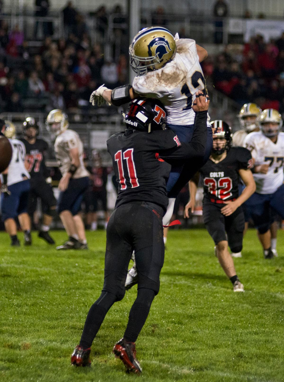 Thurston Colts defensive back Trevor Duran (#11) stops the forward motion of Marist Spartans wide receiver Hagan Stephenson (#13). Thurston defeated Marist 50 to 14 to seal the second position in their conference. Photo by Dan Morrison, Oregon News Lab