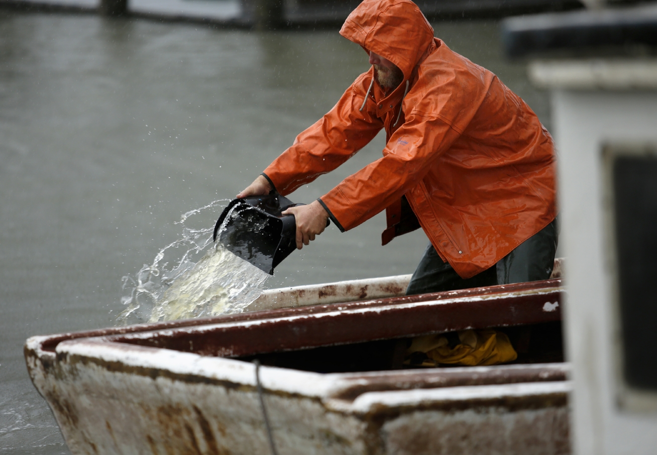 Pound net fisherman Brian Wilson bails water from one of his boats docked on Saturday, Sept.3, 2016 as Tropical Storm Hermine approaches Virginia Beach, Va.  The National Hurricane Center says Tropical Storm Hermine could bring 4 to 7 inches of rain to southeastern Virginia and the Atlantic coastal portion of Maryland as well as 1 to 4 inches of rain over southern Delaware, southern and eastern New Jersey and Long Island through Monday morning.  (Stephen M. Katz/The Virginian-Pilot via AP)
