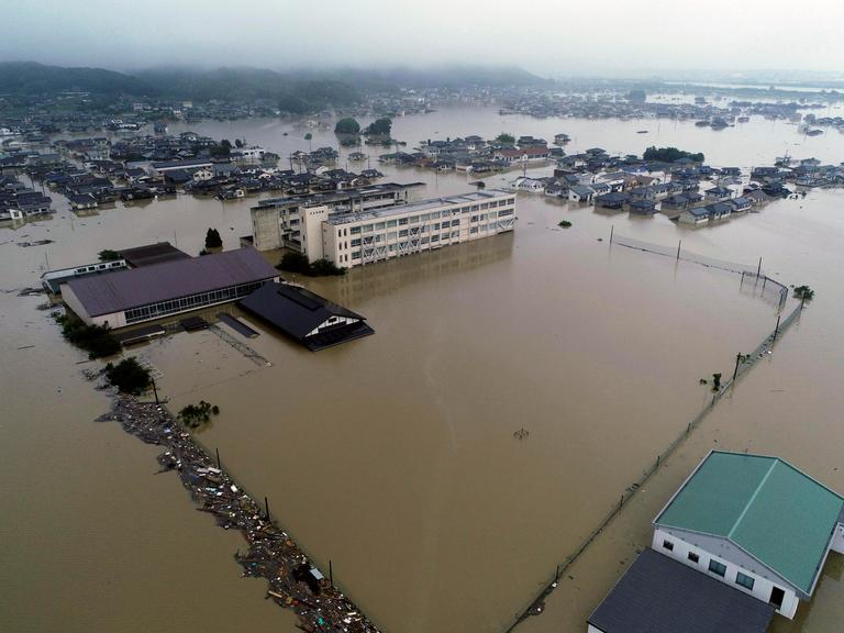 The compound of a junior high school is flooded after heavy rains in Kurashiki, Okayama prefecture, southwestern Japan, Saturday, July 7, 2018. Heavy rainfall hammered southern Japan for the third day, prompting new disaster warnings on Kyushu and Shikoku islands Sunday. (Koji Harada/Kyodo News via AP)
