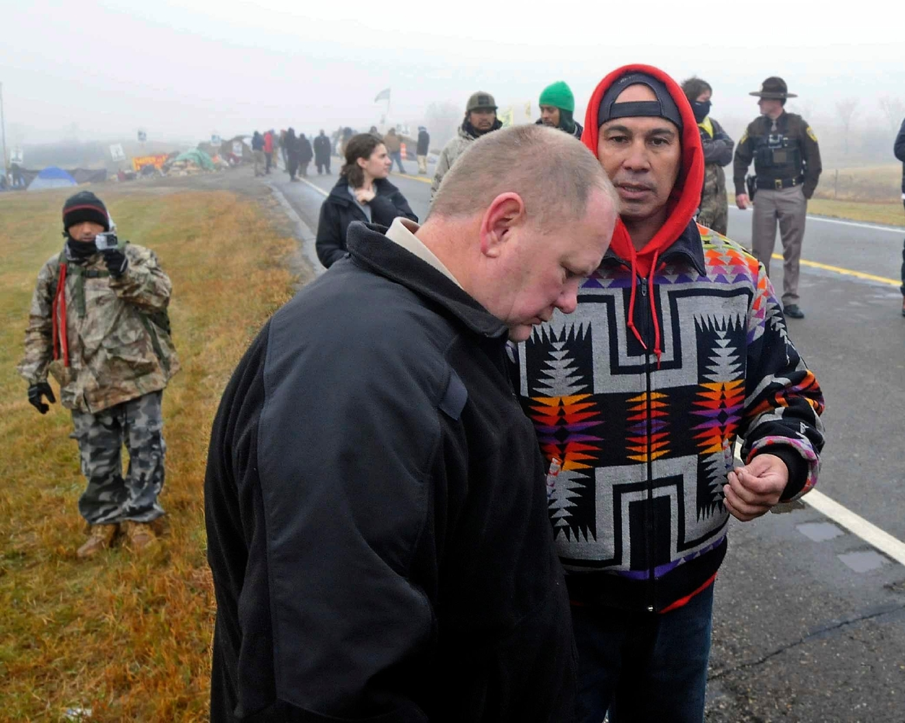 Morton County Sheriff Kyle Kirchmeier, front, listens to Brian Wesley Horinek, of Oklahoma, outside the New Camp on Pipeline Easement in North Dakota on Wednesday, Oct. 26, 2016. Sheriff Kirchmeier and Cass County Sheriff Paul Laney were at the site where a human barricade stopped traffic on North Dakota Highway 1806. The prospect of a police raid on an encampment protesting the Dakota Access pipeline faded as night fell Wednesday, with law enforcement making no immediate move after protesters rejected their request to withdraw from private land. Activists fear the nearly 1,200-mile pipeline could harm cultural sites and drinking water for the Standing Rock Sioux tribe. (Tom Stromme/The Bismarck Tribune via AP)