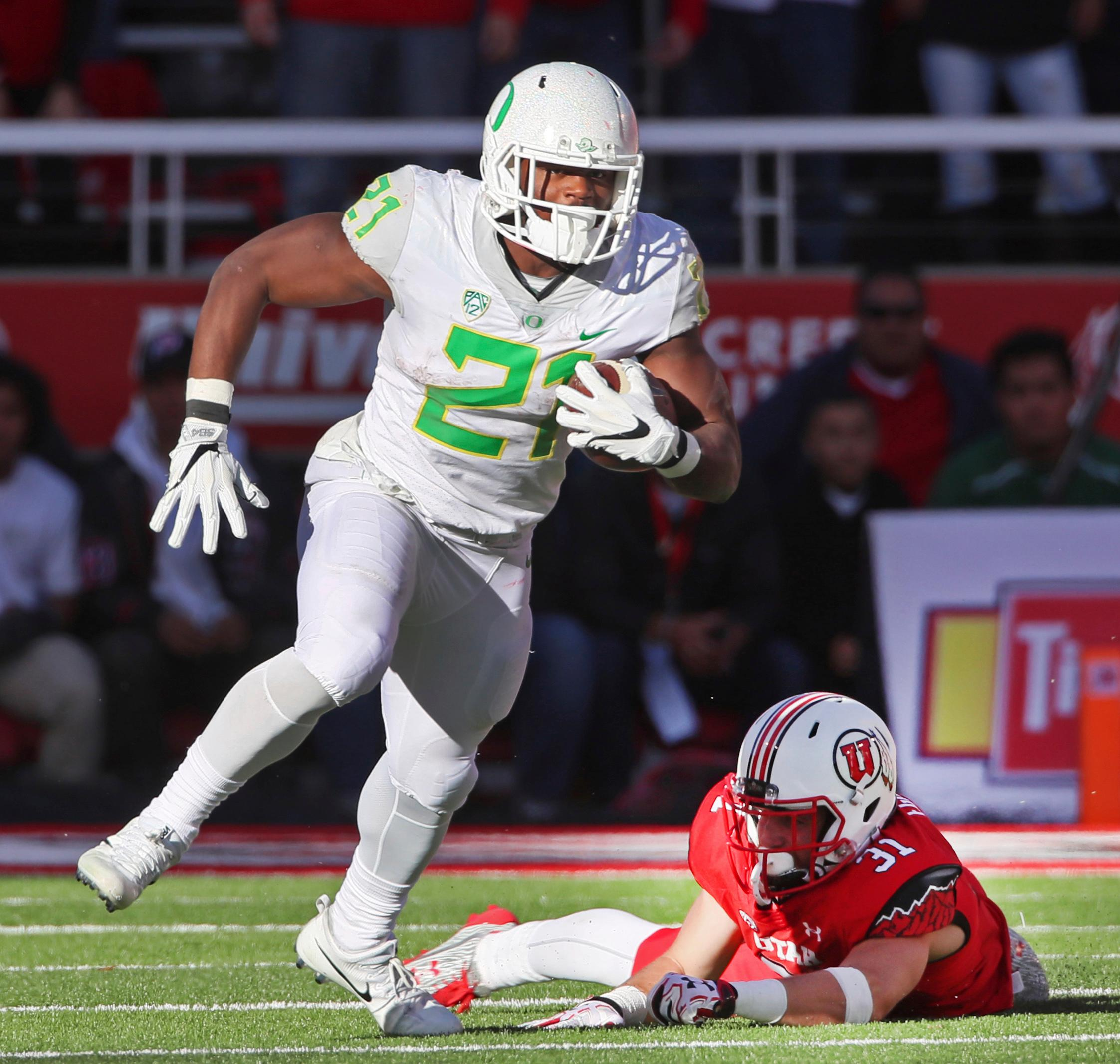 FILE - In this Nov. 19, 2016, file photo, Oregon running back Royce Freeman, left, runs past Utah linebacker Evan Eggiman in the second half of an NCAA college football game in Salt Lake City, Utah. Oregon running back Royce Freeman, USC quarterback Sam Darnold and UCLA quarterback Josh Rosen are among the Pac-12 players to keep an eye on coming out of spring practice. (AP Photo/George Frey, file)