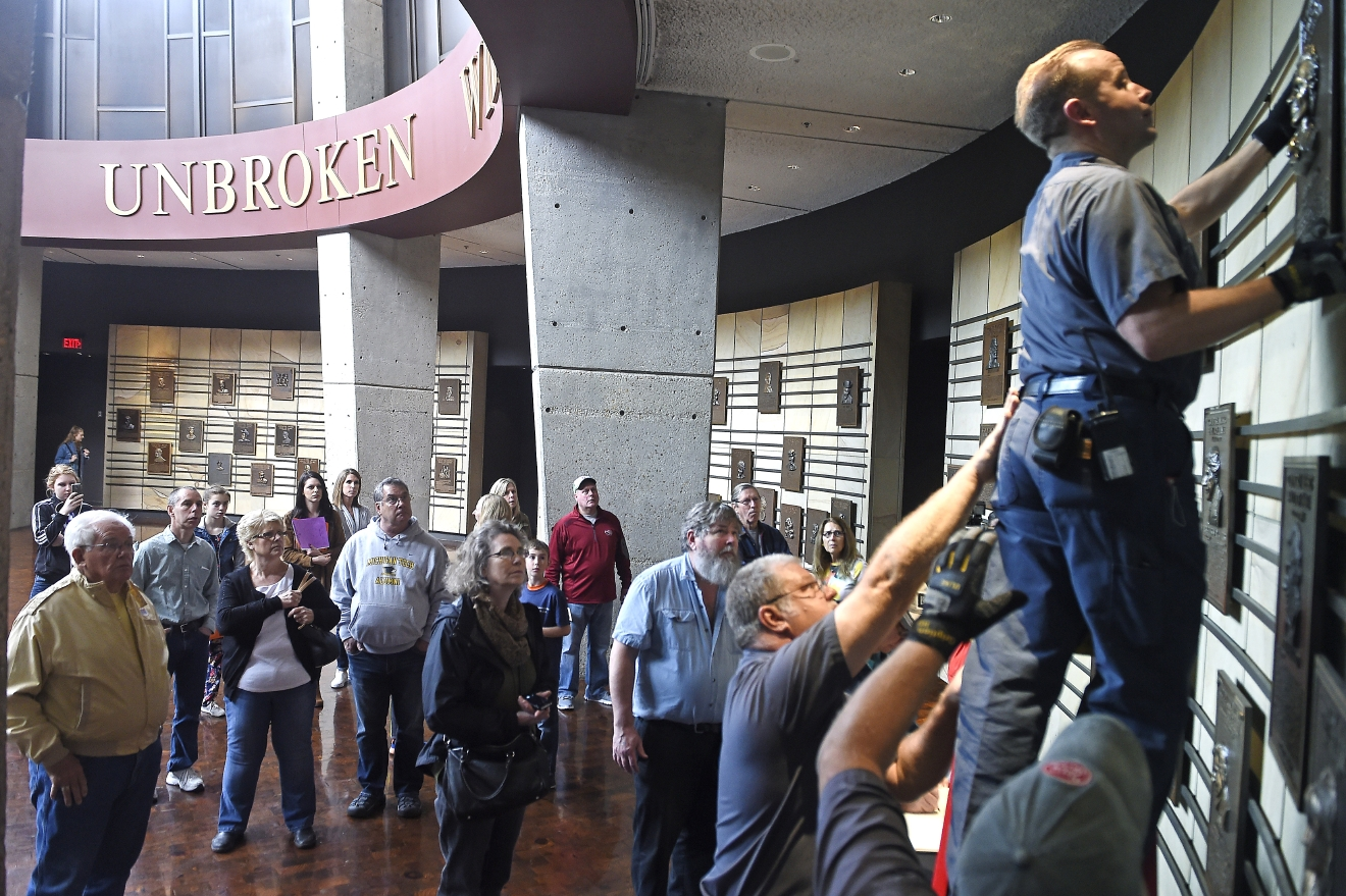 "Fans watch as Craig Alspaugh moves the plaque of Merle Haggard to a lower level as fans pay their respects to the singer in the Rotunda Hall at the Country Music Hall of Fame, Wednesday April 6, 2016, in Nashville, Tenn., after learning of his death. Haggard, who rose from poverty and prison to international fame through his songs about outlaws, underdogs and an abiding sense of national pride in such hits as ""Okie From Muskogee"" and ""Sing Me Back Home,"" died Wednesday at 79, on his birthday. (Larry McCormack/The Tennessean via AP) NO SALES; MANDATORY CREDIT"