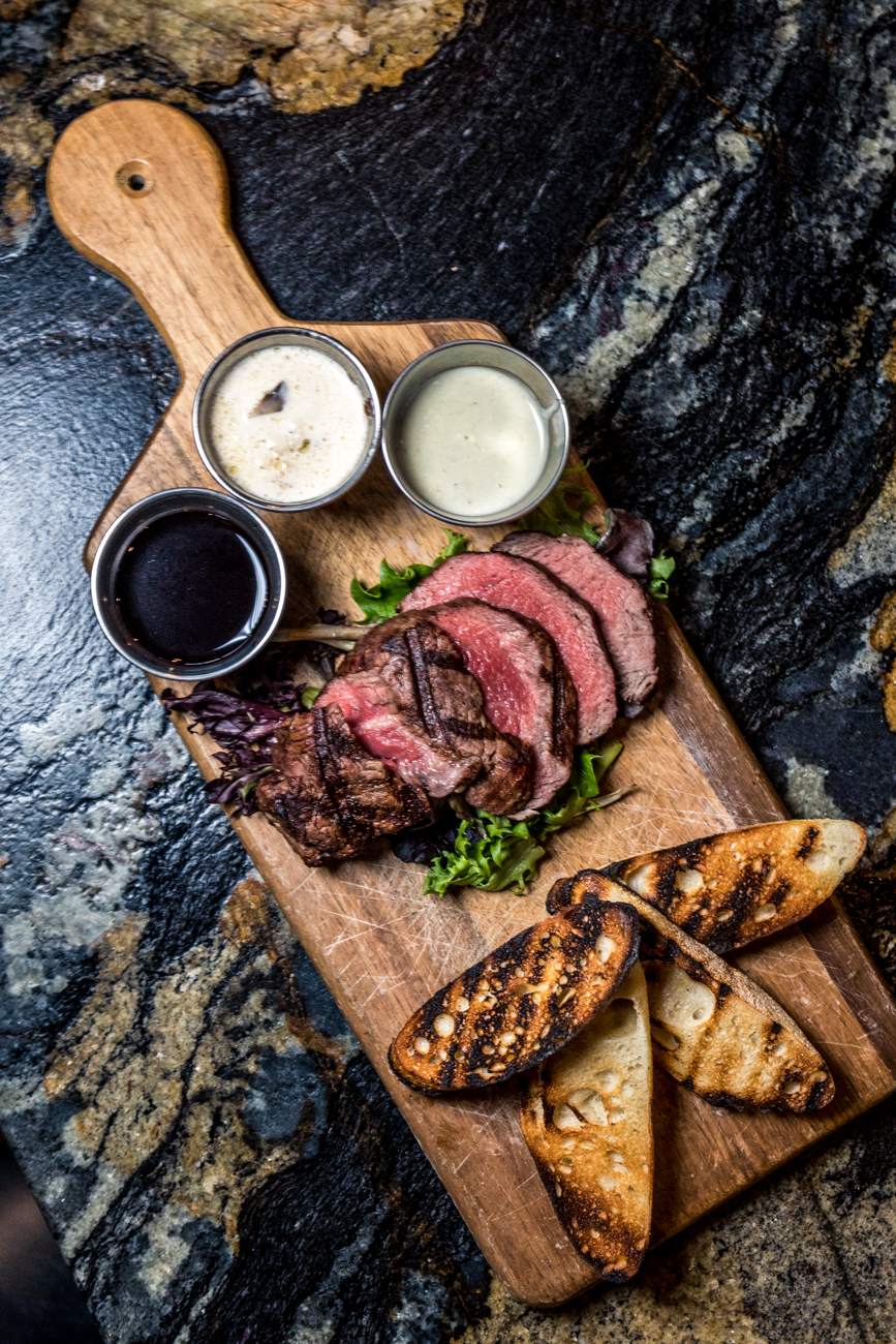 Sliced filet mignon: filet mignon thinly sliced and paired with red wine sauce, bleu cheese butter, and mushroom garlic sauce / Image: Catherine Viox // Published: 3.7.20
