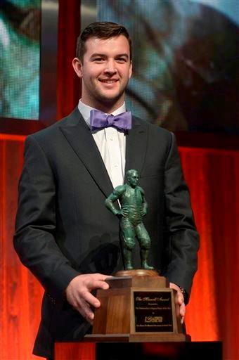 Alabama quarterback AJ McCarron poses with the Maxwell Award after winning the honor during the College Football Awards show in Lake Buena Vista, Fla., Thursday, Dec. 12, 2013.