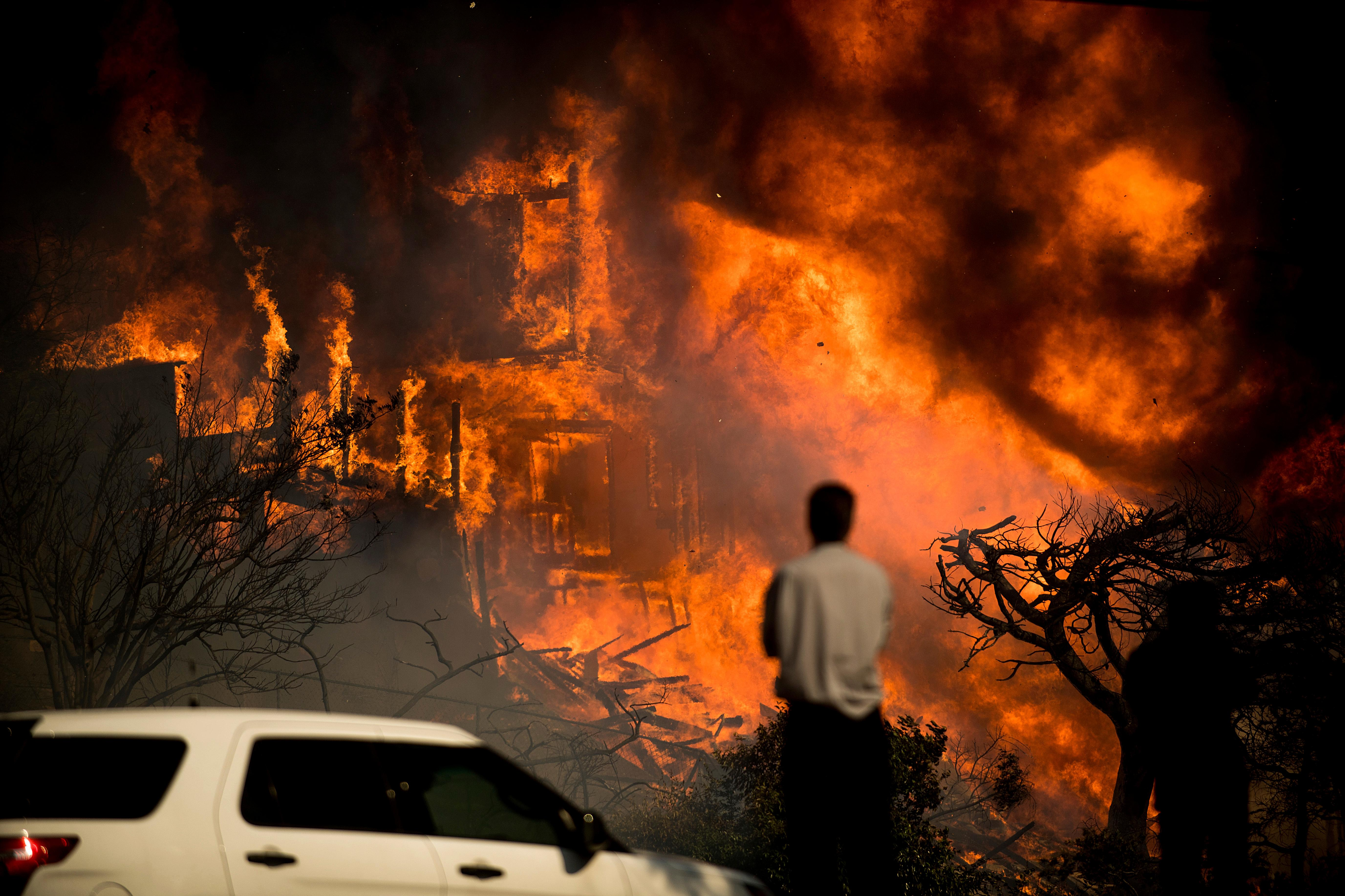 A man watches flames consume a residence as a wildfire rages in Ventura, Calif., Tuesday, Dec. 5, 2017. Ferocious winds in Southern California have whipped up explosive wildfires, burning a psychiatric hospital and scores of other structures. (AP Photo/Noah Berger)