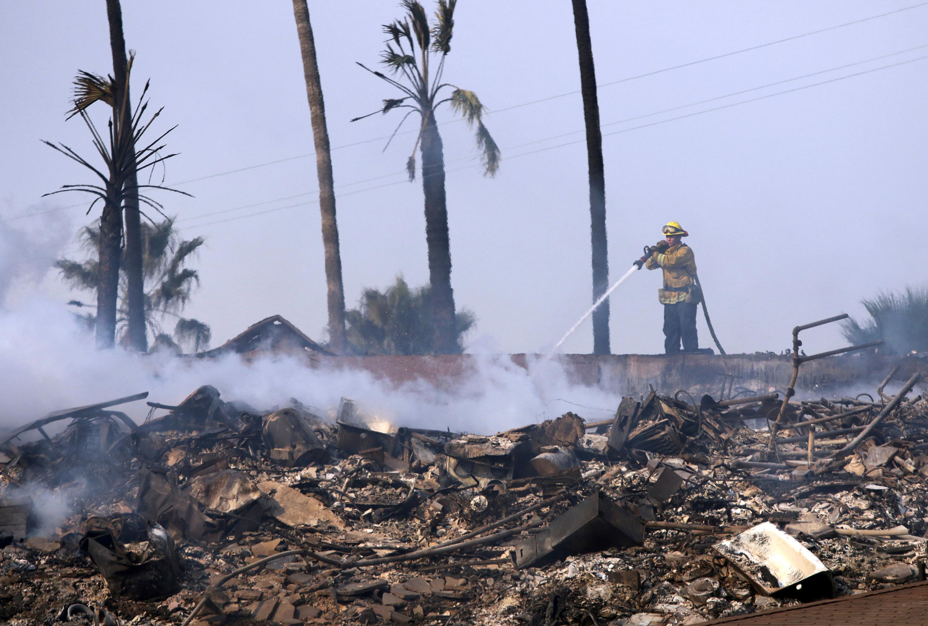 A firefighter hoses down the remains of a destroyed home after the Thomas fire swept through Ventura, Calif., Tuesday, Dec. 5, 2017. (Daniel Dreifuss via AP)