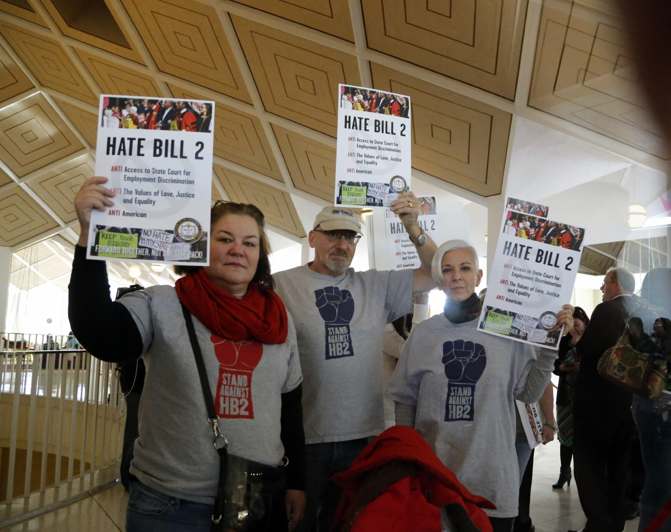 Opponents of HB2 hold signs outside the N.C. House chambers gallery as the N.C. General Assembly convenes for a special session at the Legislative Building in Raleigh, NC on Dec. 21, 2016.