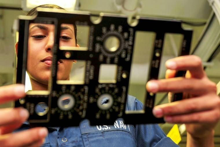 U.S. Navy Seaman Maria Pandolfo inspects a faceplate aboard the USS Ronald Reagan in the Pacific Ocean, Nov. 4, 2013. The Reagan and embarked Carrier Air Wing 2 are conducting carrier qualifications. Pandolfo is an aviation electrician's mate airman.