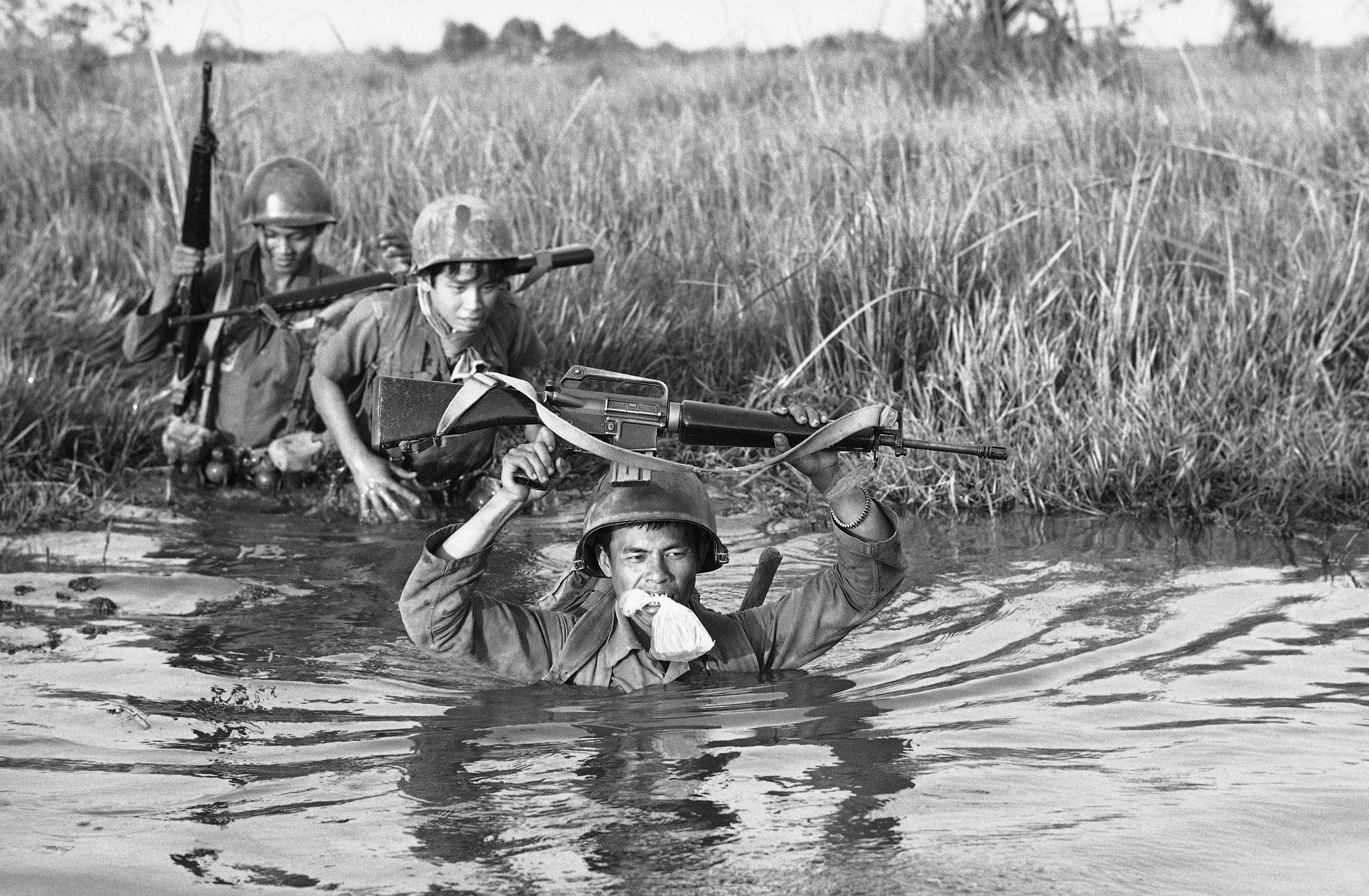 In this March 11, 1972, file photo, a South Vietnamese soldier holds his personal belongings in a plastic bag between his teeth as his unit crosses a muddy Mekong Delta stream in Vietnam near the Cambodian border. His unit was charged with stemming Communist infiltration from Cambodia into South Vietnam in the heavily populated Mekong Delta area. NICK UT/THE ASSOCIATED PRESS
