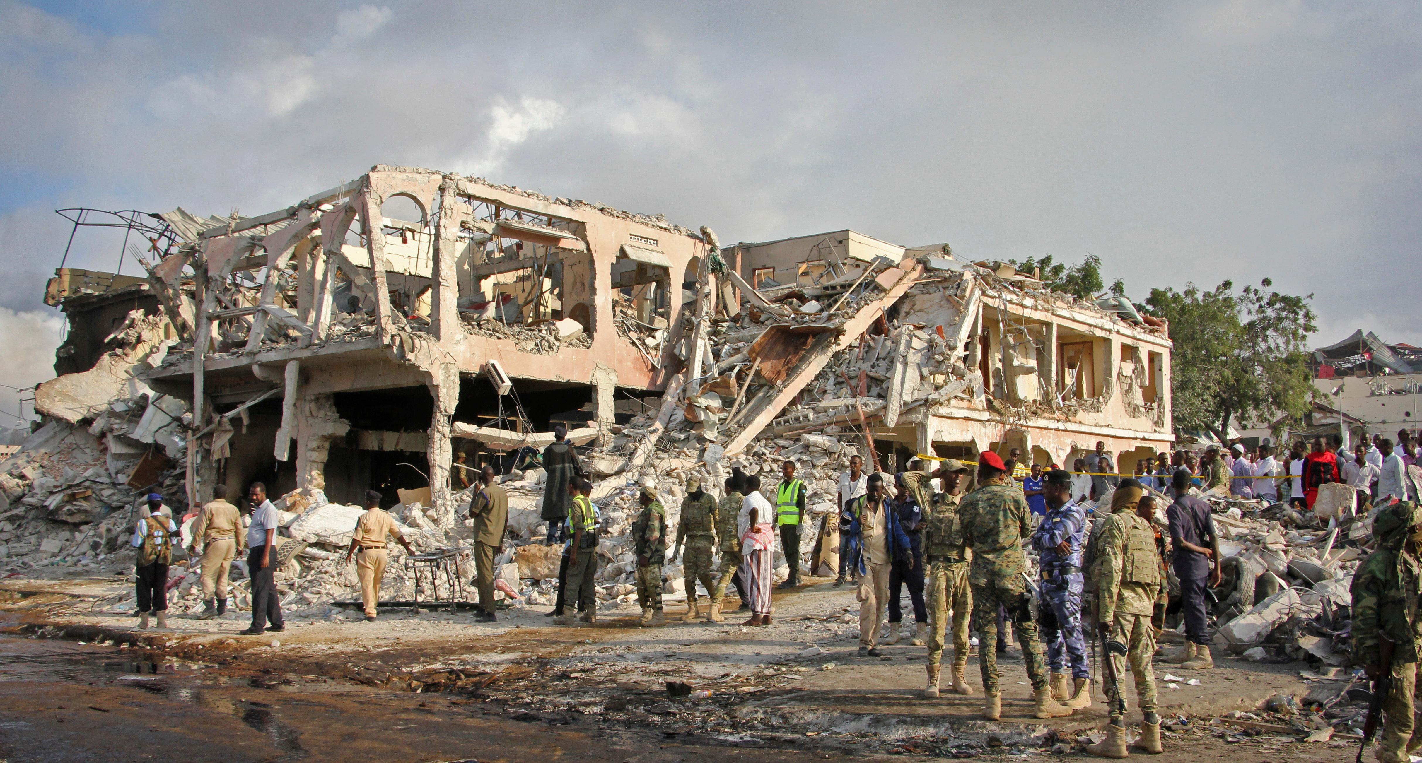 Somali security forces and others gather and search for bodies near destroyed buildings at the scene of Saturday's blast, in Mogadishu, Somalia Sunday, Oct. 15, 2017. The death toll from the huge truck bomb blast in Somalia's capital rose to over 50 Sunday, with more than 60 others injured, as hospitals struggled to cope with the high number of casualties, security and medical sources said. (AP Photo/Farah Abdi Warsameh)