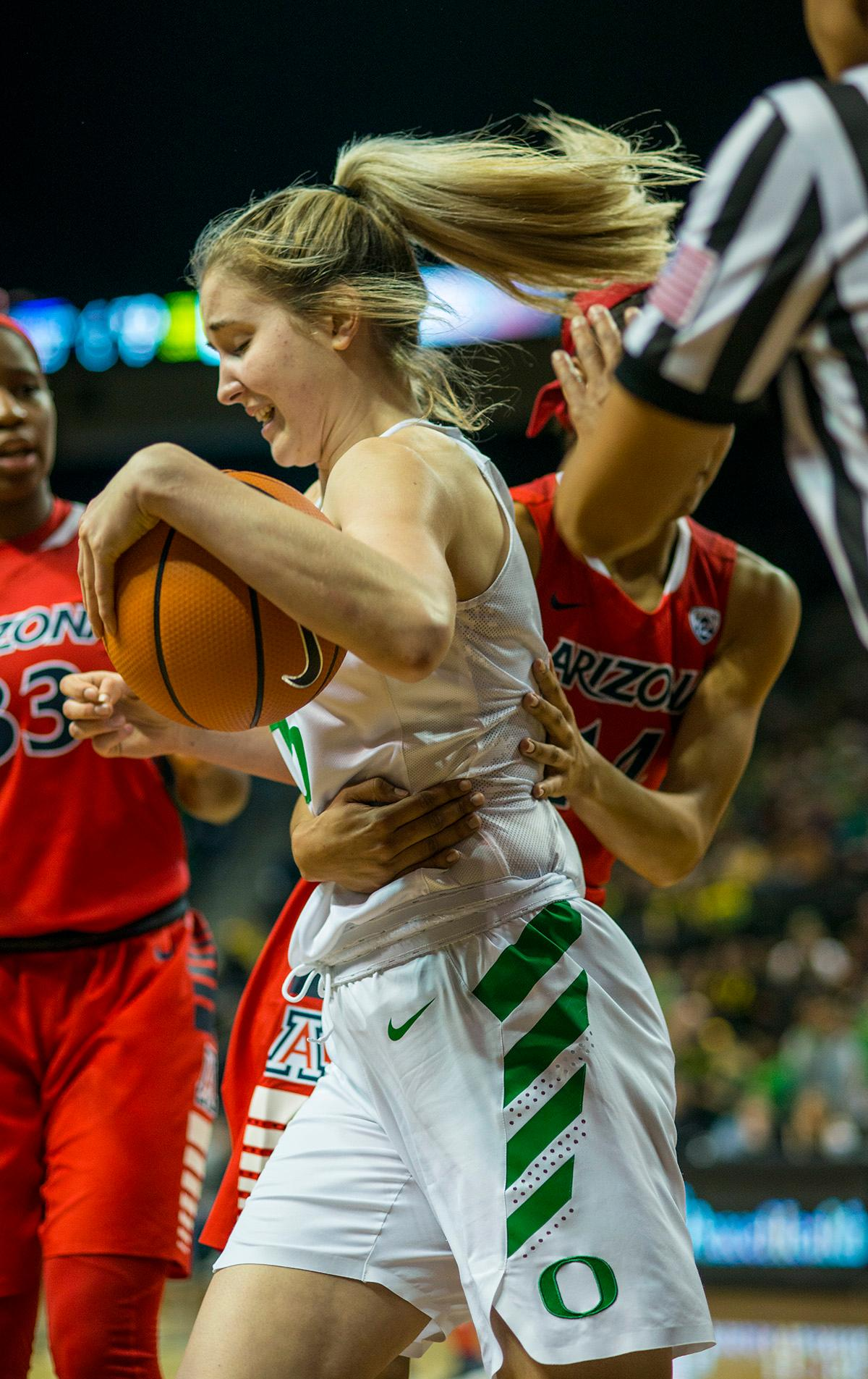 Oregon Ducks Anneli Maley (#15) attempts to keep control of the ball as she is grabbed by Arizona Wildcats Sam Thomas (#14). The Oregon Ducks defeated the Arizona Wildcats 62-44 on Friday night at Matthew Knight Arena. The Ducks are now 5-0 in conference play, for the first time in school history, and first place in Pac 12. Sabrina Ionescu led with 22 points including four three-pointers and eleven rebounds. Ruthy Hebard added 14 points. Photo by Rhianna Gelhart, Oregon News Lab