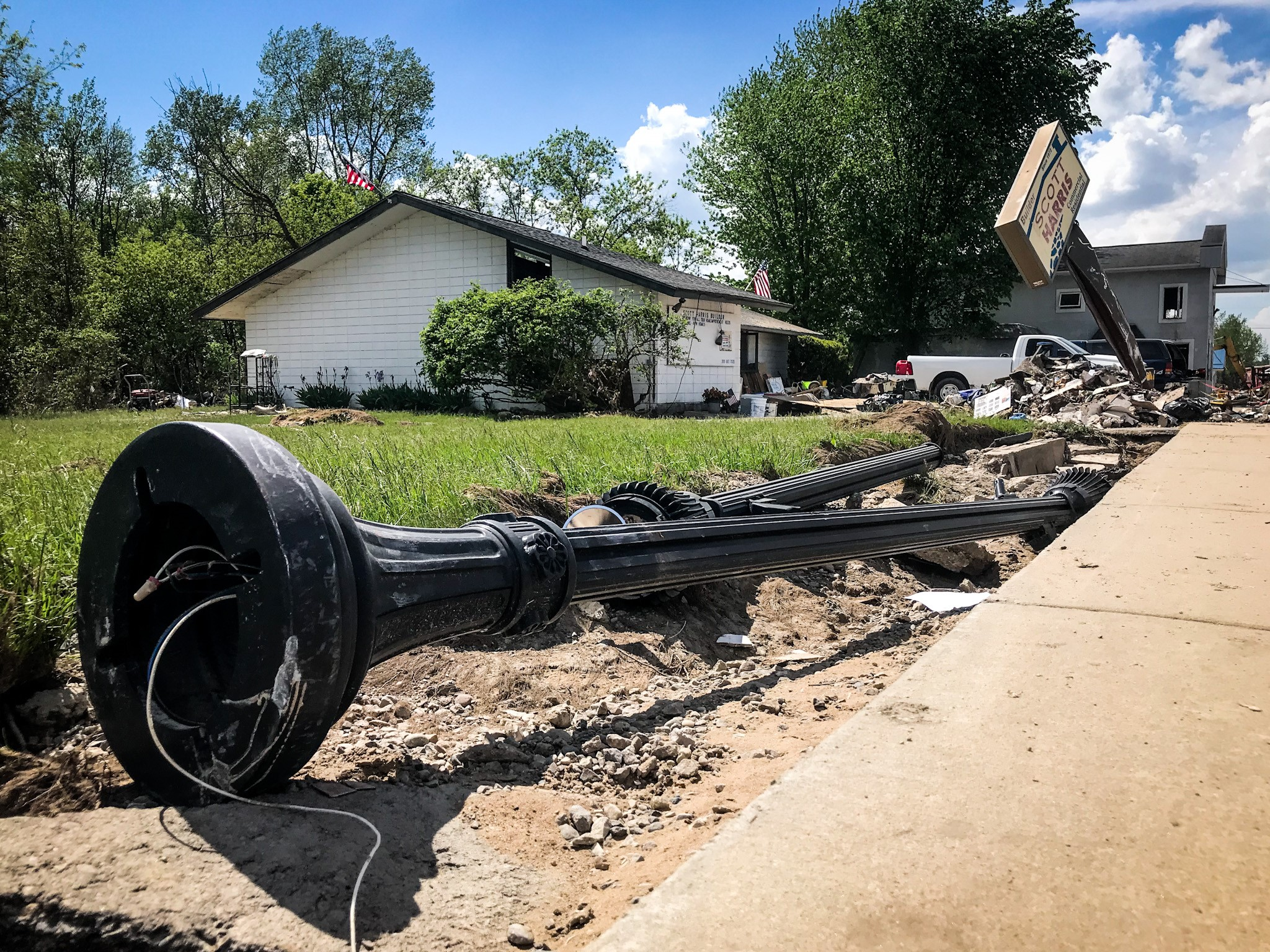 A surge of rushing water from Wixom lake causes a light pole to fall in downtown Sanford. Picture was taken on May 27, 2020. (WWMT/Mikenzie Frost)