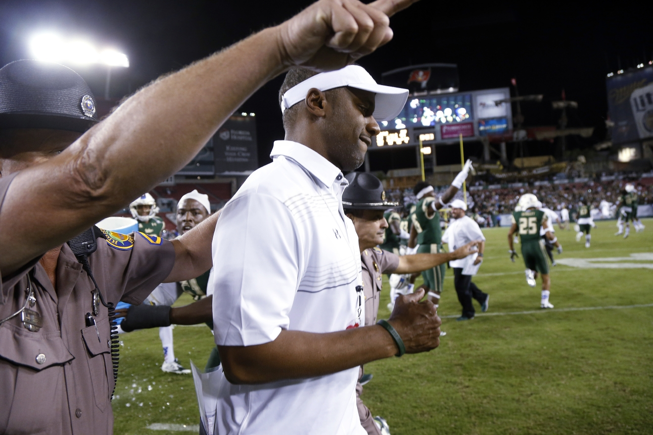 FILE - In this Nov. 14, 2015, file photo, South Florida coach Willie Taggart runs onto the field after South Florida's 44-23 win over Temple in an NCAA college football game,   in Tampa, Fla. South Florida football coach Willie Taggart has informed the school that he is leaving to become the coach at Oregon, a person with direct knowledge of the situation tells The Associated Press. The person spoke on condition of anonymity because neither school was prepared to make an official announcement. (AP Photo/Brian Blanco, File)