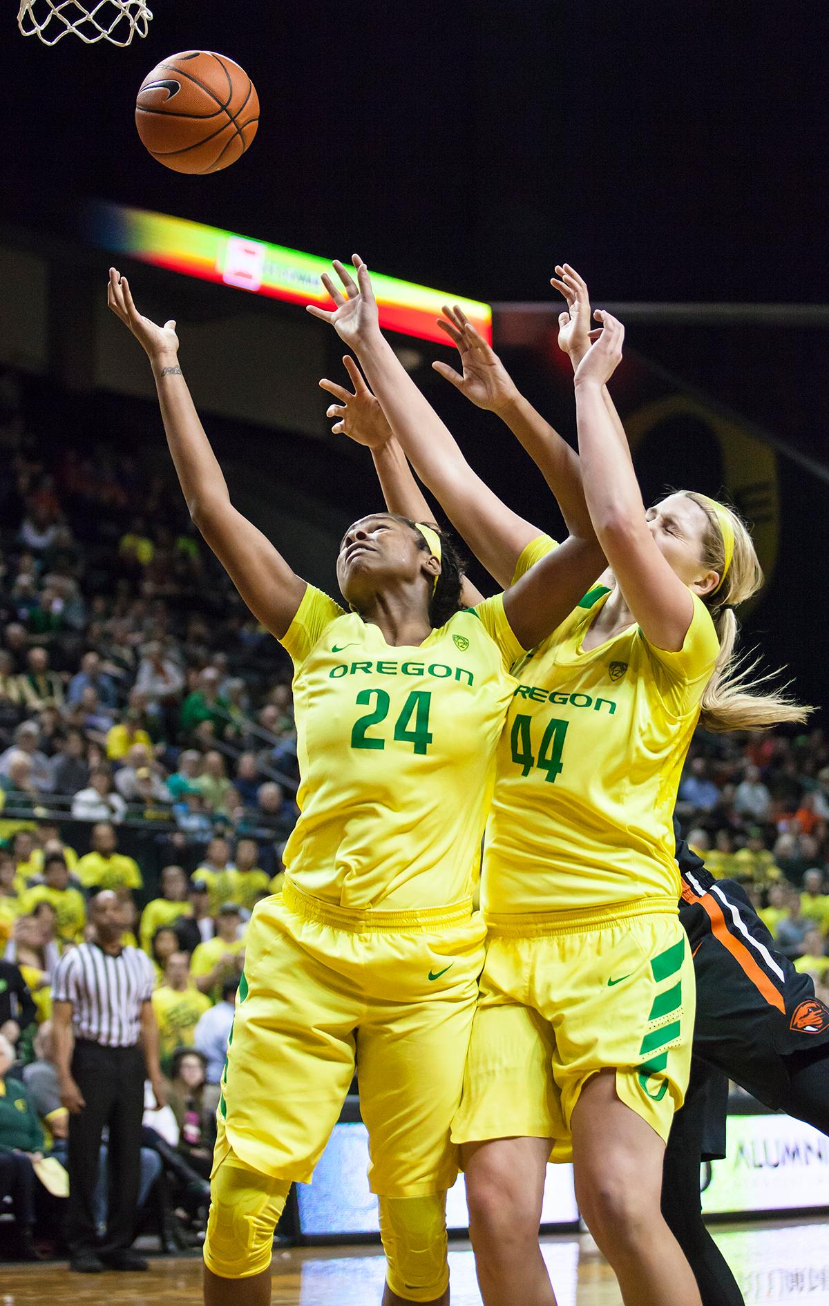 Oregon forwards Mallory McGwire (#44) and Ruthy Hebard (#24) reach out to catch a rebounded shot. The Oregon Ducks lost 40 to 43 against the Oregon State Beavers after a tightly matched 4th quarter. Photo by Ben Lonergan, Oregon News Lab