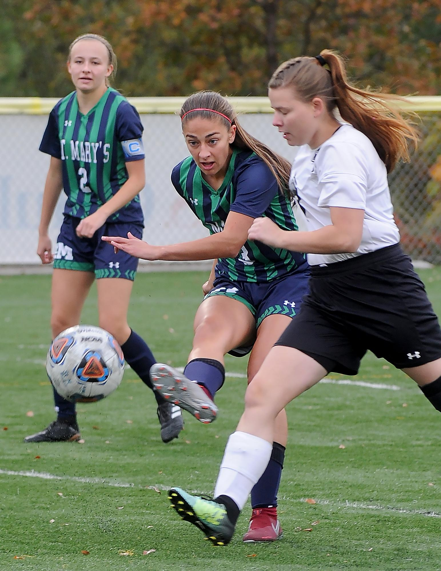 Maddie Wheelock, (3). scores a goal in the first half against Trojan defender Chayanne Van Allen, (4), as St. Mary's forward Meghan Michels, (2), looks on. Photo by Denise Baratta