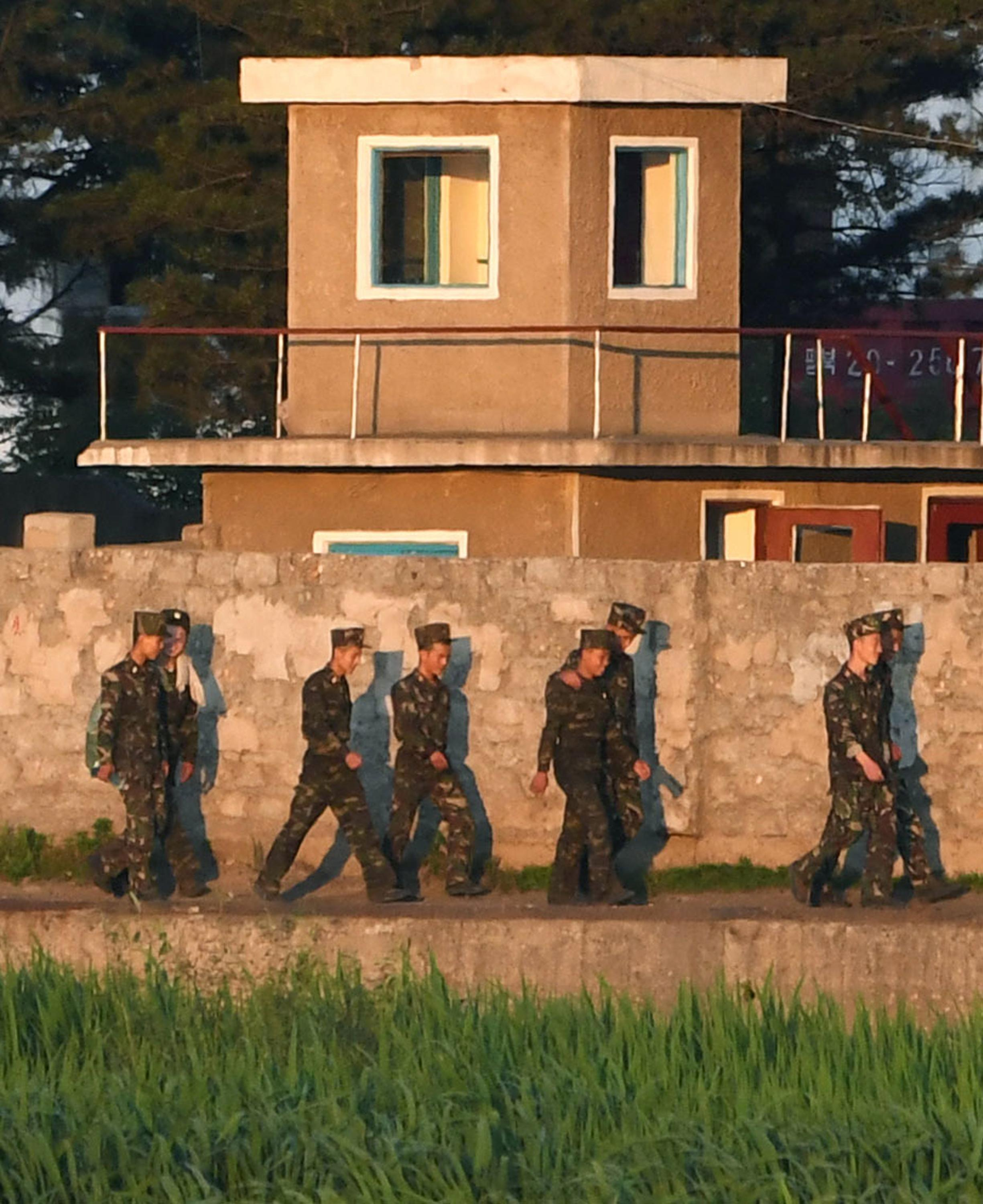 In this Tuesday, July 4, 2017 photo, North Korean soldiers walk in border town of Simuiju, North Korea, as they are seen from Dandong, northeastern Liaoning province of China. (Minoru Iwasaki/Kyodo News via AP)
