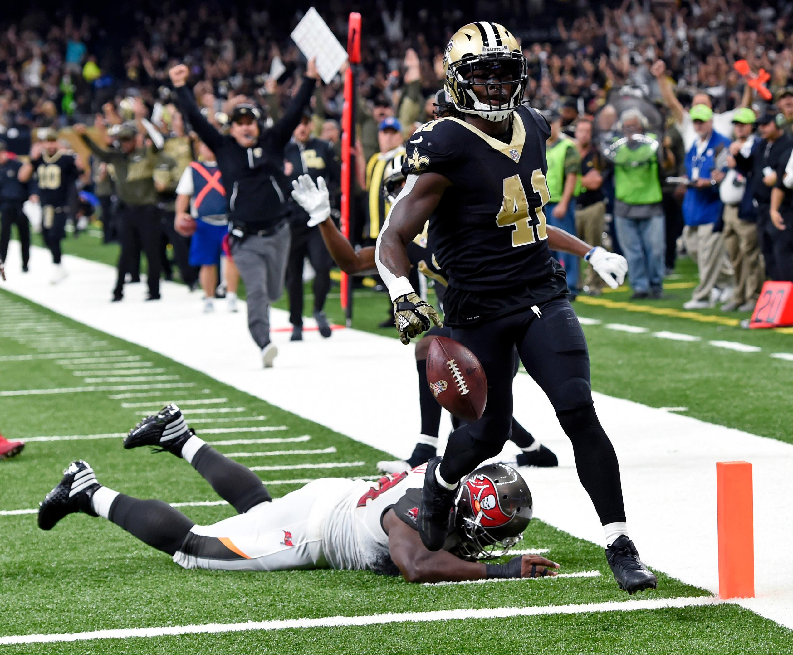 FILE - In this Sunday, Nov. 5, 2017, file photo, New Orleans Saints running back Alvin Kamara (41) carries for a touchdown past a diving Tampa Bay Buccaneers defensive tackle Clinton McDonald in the first half of an NFL football game in New Orleans. Texans quarterback Deshaun Watson probably had surpassed Kareem Hunt, Leonard Fournette and Alvin Kamara when he went down before Week 9 with a torn ACL. That seems to put the race for this award in the cleats of those running backs.  (AP Photo/Bill Feig, File)