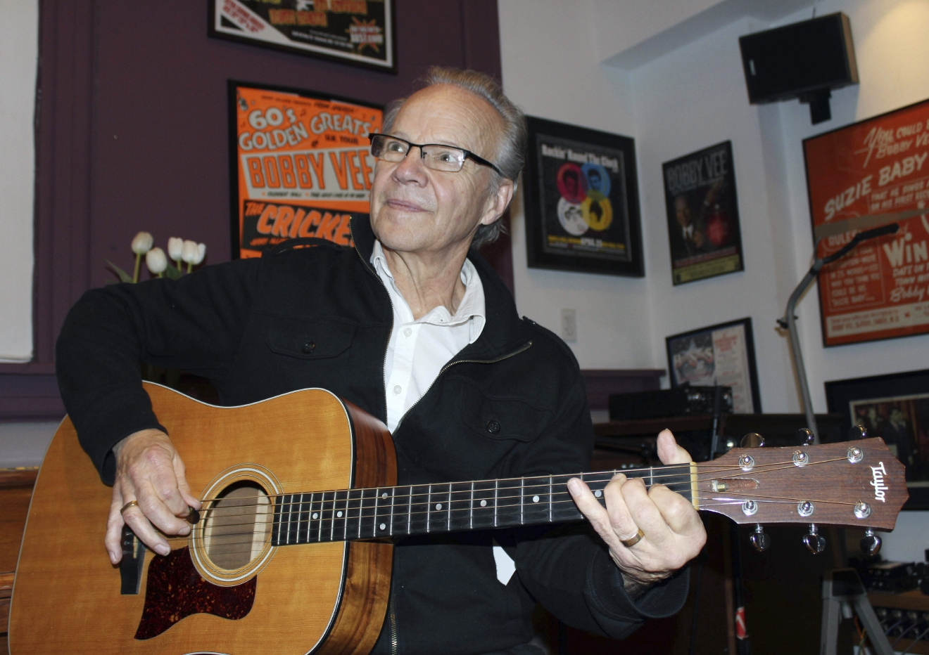 FILE - In this Dec. 18, 2013 file photo, Bobby Vee plays the guitar at his family's Rockhouse Productions in St. Joseph, Minn. Vee, whose rise toward stardom began as a 15-year-old fill-in for Buddy Holly after Holly was killed in a plane crash, died Monday Oct. 24, 2016 of complications from Alzheimer's disease. He was 73. (AP Photo/Jeff Baenen, File)