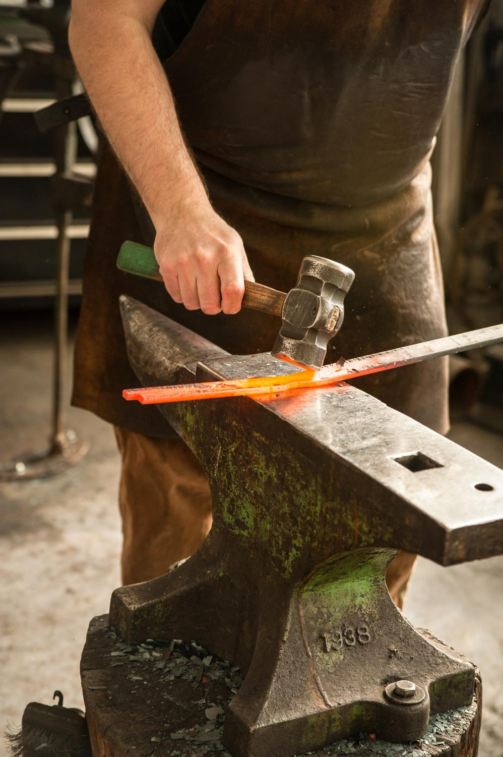 Gilsdorf hammers a bar of steel, blazing hot from the forge. / Image: Melissa Doss Sliney