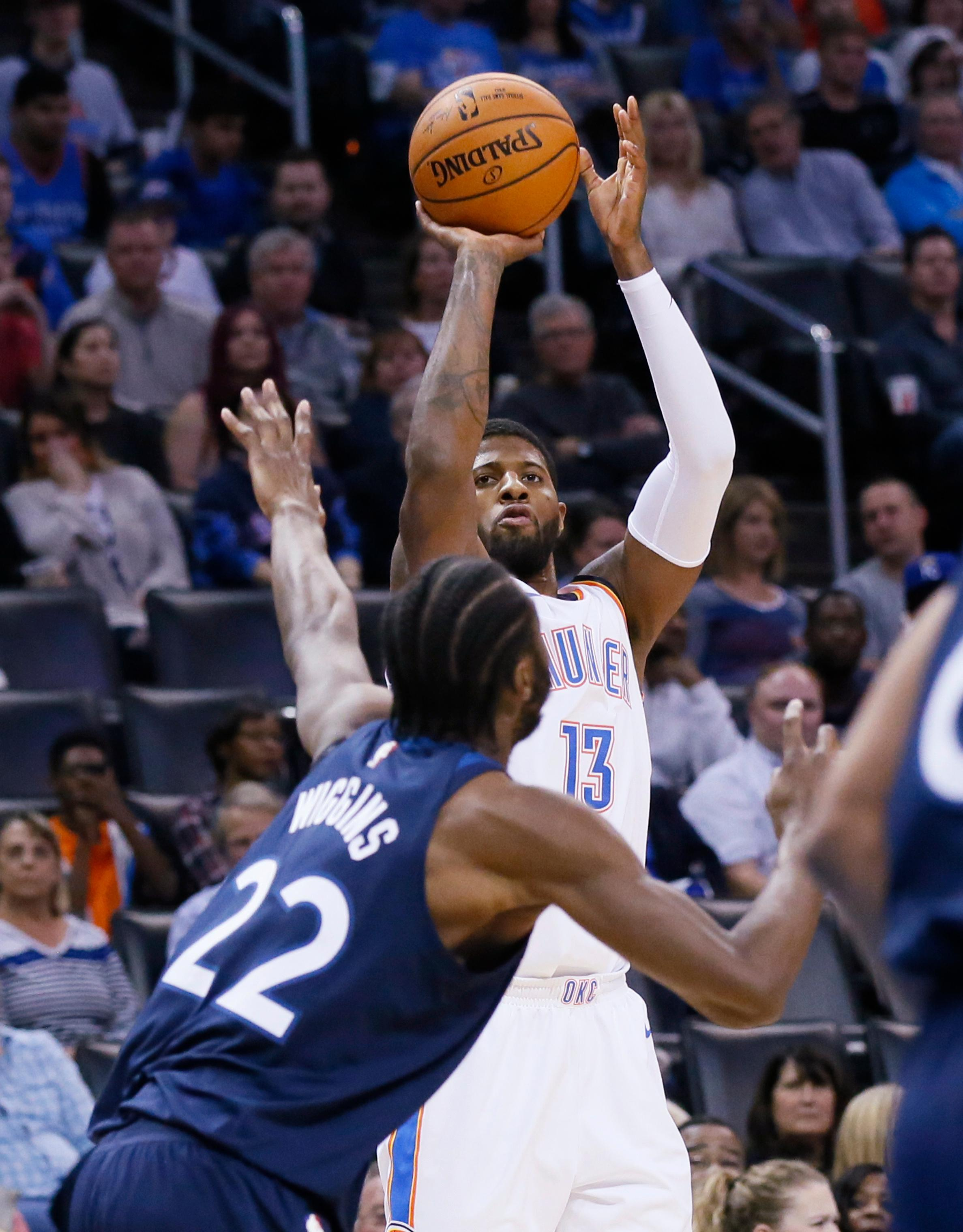 Oklahoma City Thunder forward Paul George (13) shoots over Minnesota Timberwolves forward Andrew Wiggins (22) during the first quarter of an NBA basketball game in Oklahoma City, Friday, Dec. 1, 2017. (AP Photo/Sue Ogrocki)