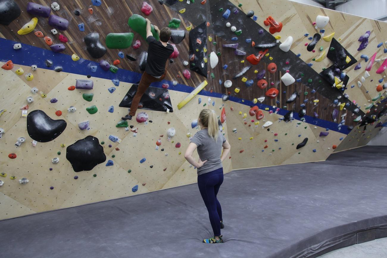A climbing partner looks on, offering advice and encouragement to her friend as she boulders. / Image: Chez Chesak // Published: 2.1.20