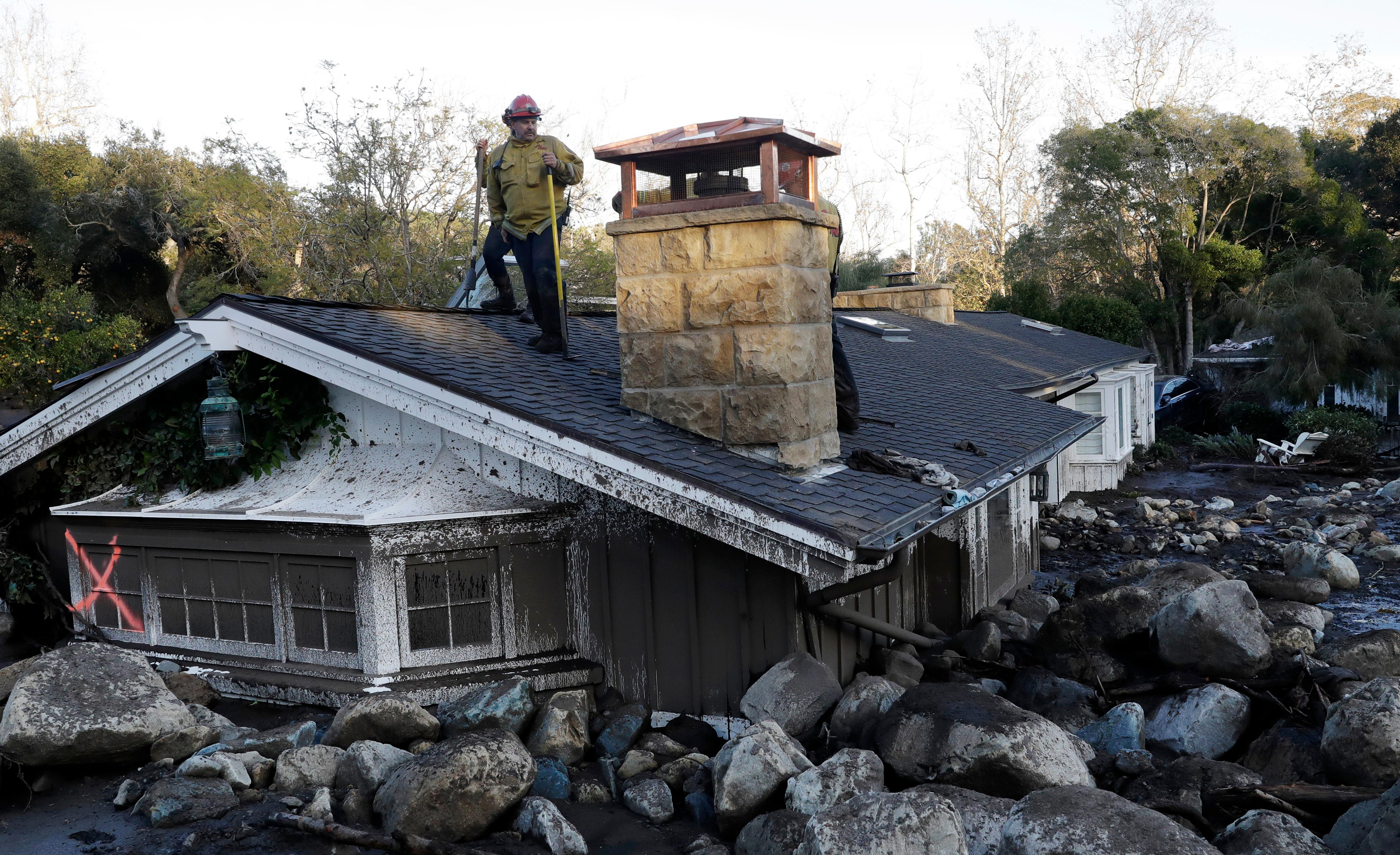 A firefighter stands on the roof of a house submerged in mud and rocks Wednesday, Jan. 10, 2018, in Montecito, Calif. Anxious family members awaited word on loved ones Wednesday as rescue crews searched grimy debris and ruins for more than a dozen people missing after mudslides in Southern California destroyed houses, swept cars to the beach and left more than a dozen victims dead. (AP Photo/Marcio Jose Sanchez)