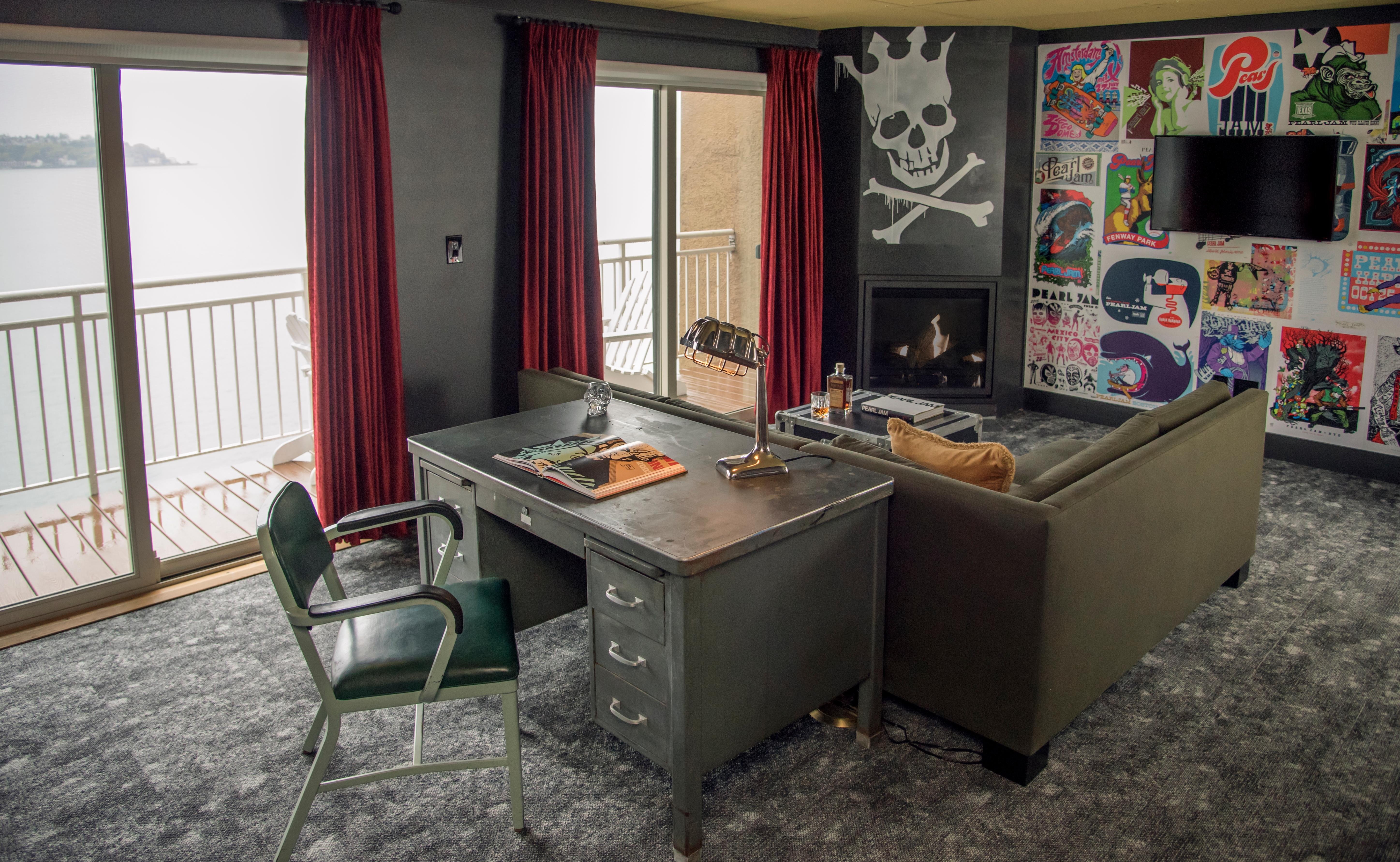 Pearl Jam Suite. In 2018 The Edgewater debuted the Pearl Jam Suite designed by local Seattle firm Mallet Architecture & Design and serves as yet another nod to the hotel's rich music history. Historic tour posters adorn the space, as well as a vintage Oriental rug, L-shaped couch, floor lamps activated by a guitar pedal, and a new custom bed, among other unique décor. Guests can indulge in the ultimate rock 'n' roll experience in the Pearl Jam Suite, which includes large wall graphics of Pearl Jam fans, a Pearl Jam curated library of books, vinyl turn table and cassette players, guitar and fender amps for guest check-out, street art of Pearl Jam-related iconography adorned on the walls and furniture, set-lists from past shows, a state of the art sound system, and much more. (Image courtesy of Edgewater Hotel)