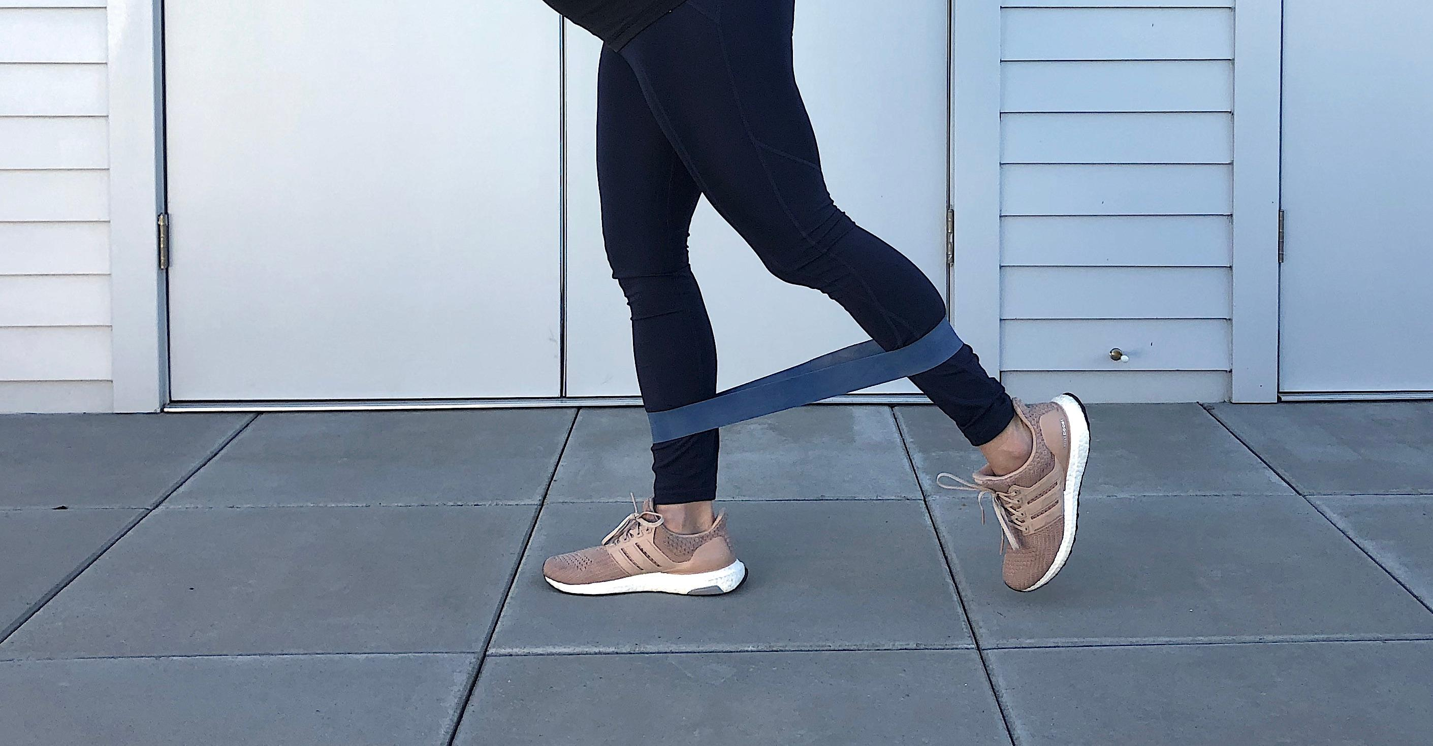 Place the band above your ankles. Stand with feet about hip width apart and have your hands on your hips or place gently against a wall for help balancing. Keep your legs mostly straight with a micro bend at the knee. Press one leg back and feel the tension in the band and the work in your glutes. (Image: Amanda Shapin)