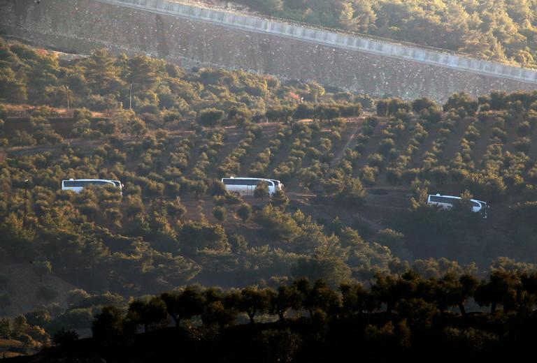 "A convoy of buses believed to be carrying Syrian opposition fighters, travels along the border with Syrias as see from the outskirts of the border town of Kilis, Turkey, Saturday, Jan. 20, 2018. Turkish jets have begun an aerial offensive, codenamed operation ""Olive Branch"", against the Syrian Kurdish-held enclave of Afrin, in northwest Syria . A military statement says the operation launched Saturday aims to protect Turkey's borders, ""neutralize"" Syrian Kurdish fighters in the enclave and to save the local population from their ""pressure and oppression."" (AP Photo/Lefteris Pitarakis)"