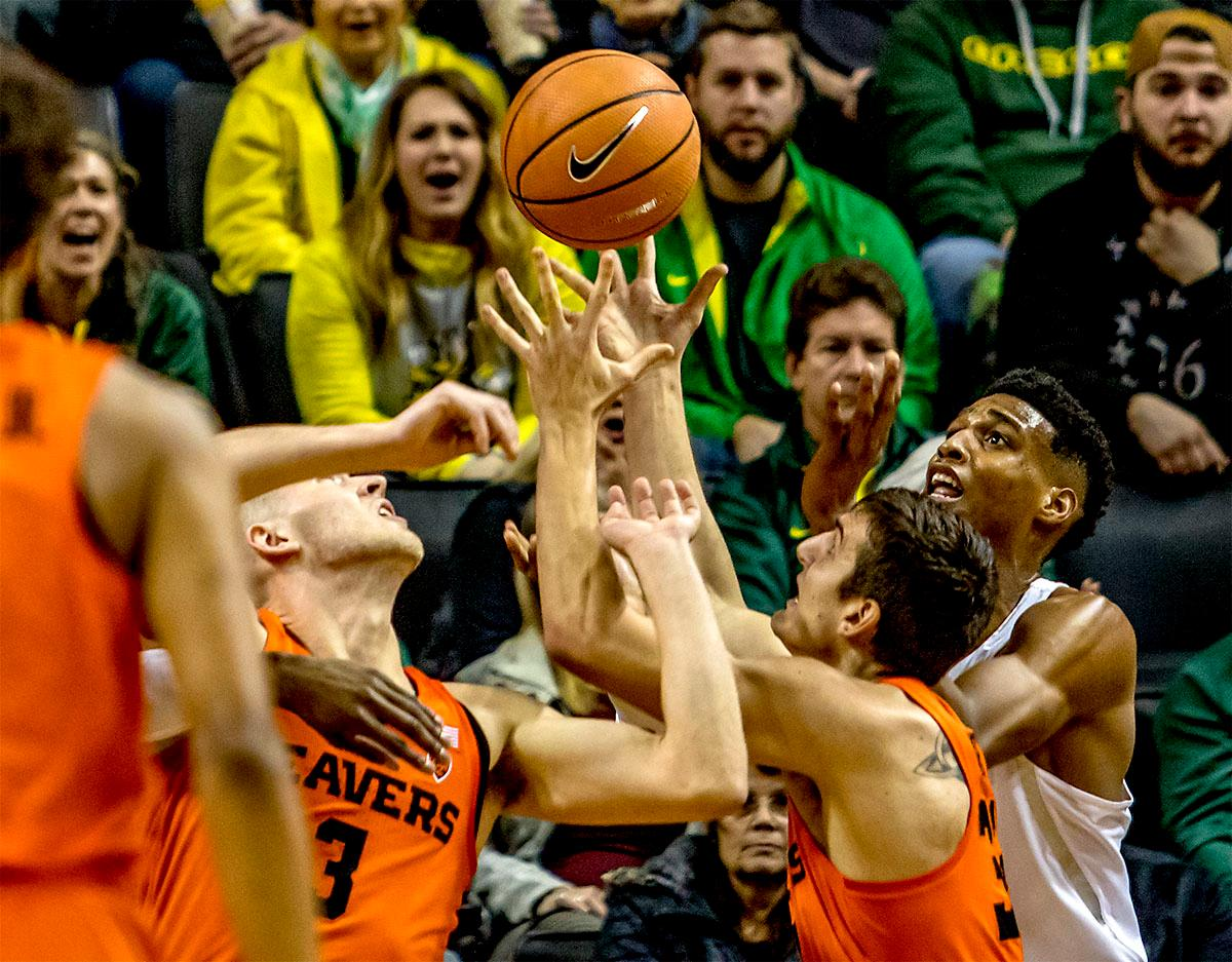 The Beavers fight under the basket to get the rebound against the Ducks. The Ducks defeated the Beavers in the civil war game, 66-57, at Matthew Knight Arena on Saturday night. Elijah Brown scored a game high of 20 points with 18 of the points coming in the first half, Paul White added 17 points. The Ducks are now 14-7 overall and 4-4 in conference play. The Ducks will next face California on Thursday Feb. 1 at 6:00 p.m. Photo by August Frank, Oregon News Lab