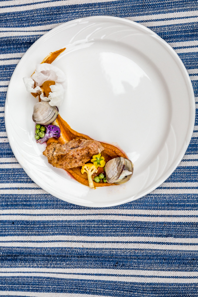 Alligator and clams: peas, carrot ravioli, purple cauliflower, blue cheese stuffed clam, micro greens, blue consume, and potato glass / Image: Catherine Viox // Published: 6.18.19