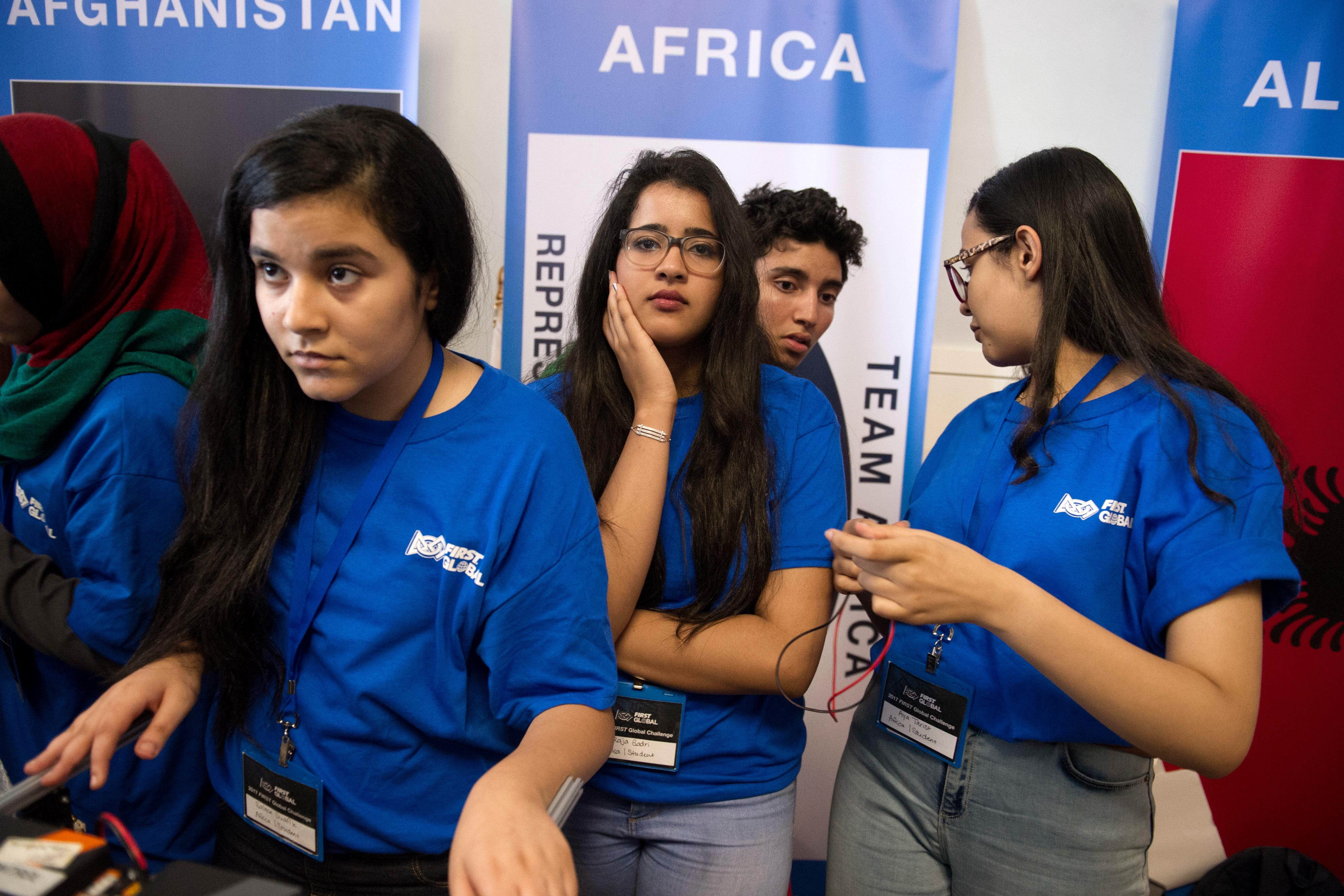 Africa team members Salma Ouafik, left, Raja Godri, center, and Aya Tarist, right, wait for the opening ceremony for the FIRST Global Challenge 2017, in Washington, Sunday, July 16, 2017. They will be competing against entrants from more than 150 countries in the FIRST Global Challenge. It's the first annual robotics competition designed to encourage youths to pursue careers in math and science.  (AP Photo/Cliff Owen)