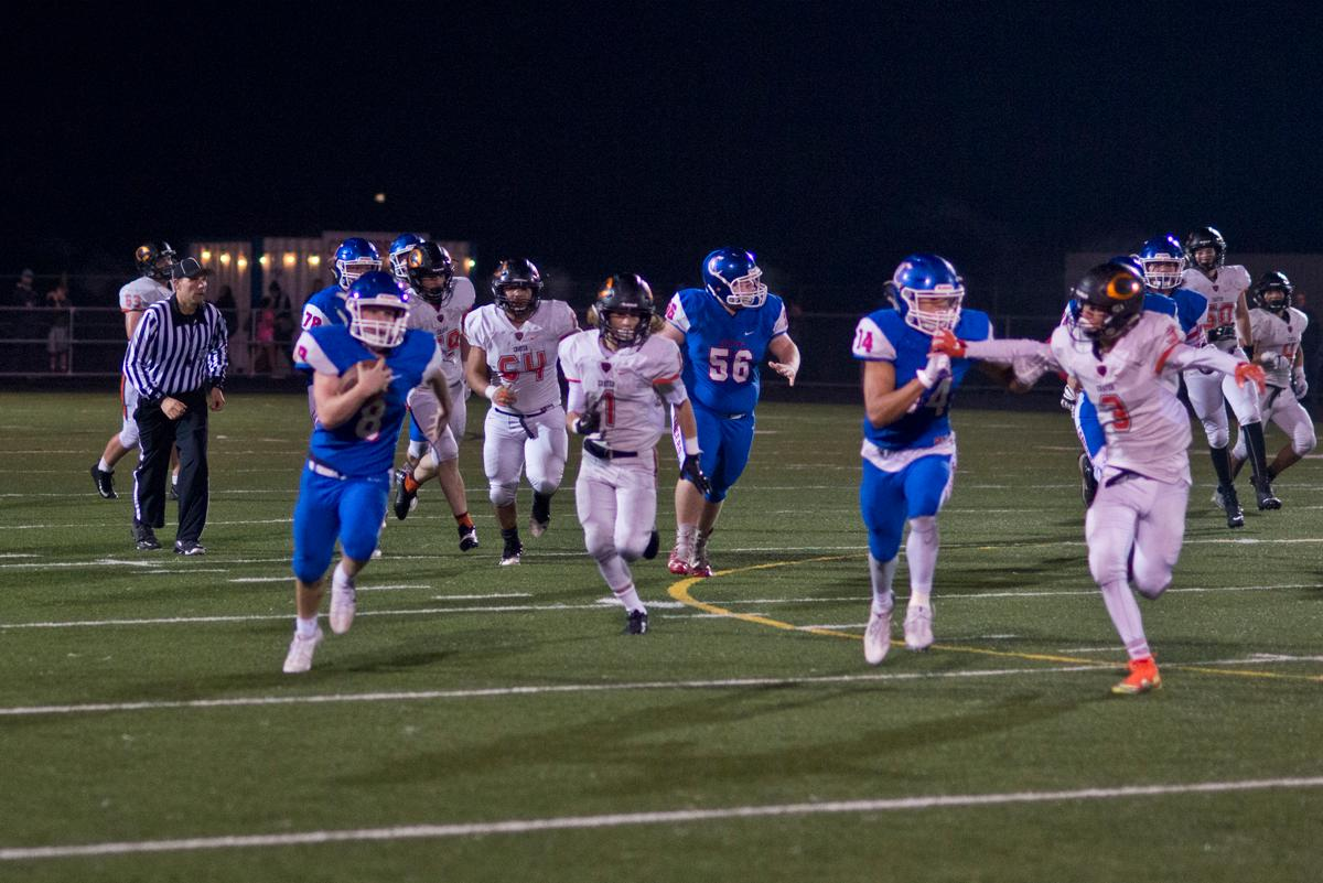 Churchill Lancers running back Dalton McDaniel (#8) sprints toward the end zone for a score against the Crater Comets. Churchill defeated Crater 63-21 on Friday at their homecoming game. Churchill remains undefeated with a conference record of 9-0. Photo by Dan Morrison, Oregon News Lab